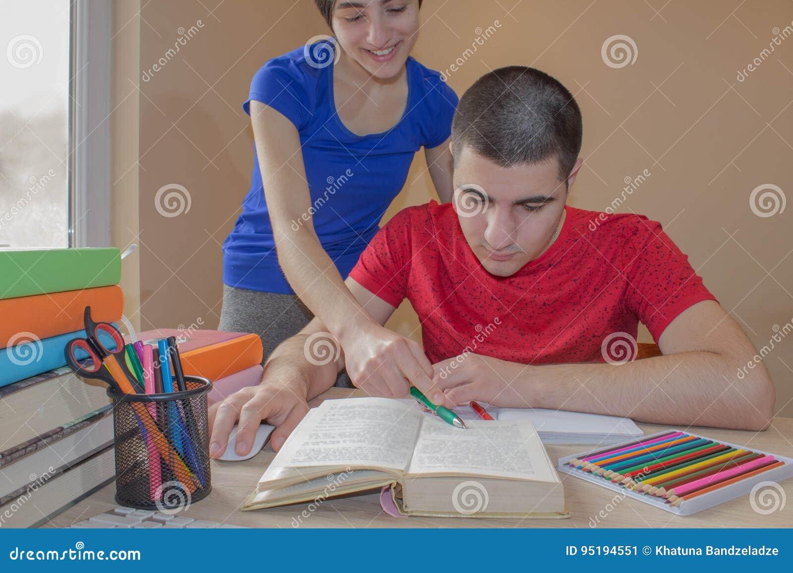 Αδελφή και αδελφός σπουδαστών που μελετούν μέσα, που διαβάζουν τα βιβλία στο γραφείο στο καθιστικό