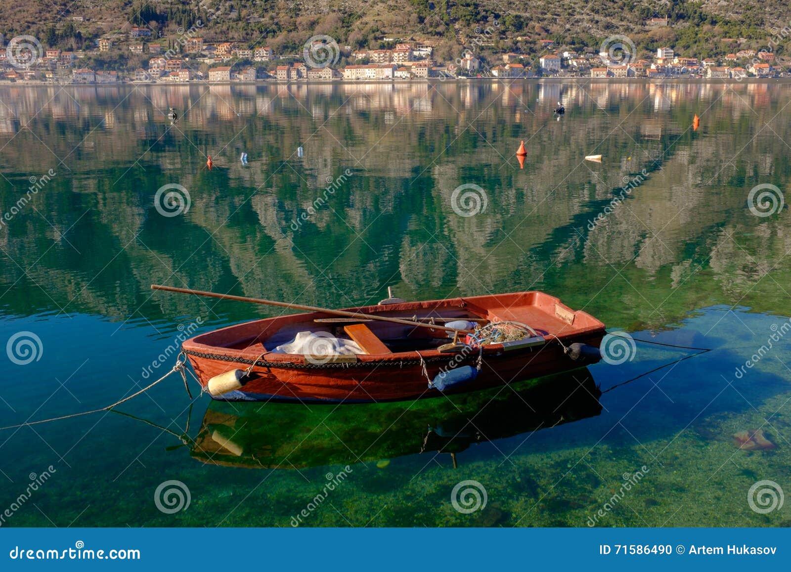 Αλιευτικό σκάφος στο σαφές νερό, την παλαιά πόλη και τα βουνά στο υπόβαθρο