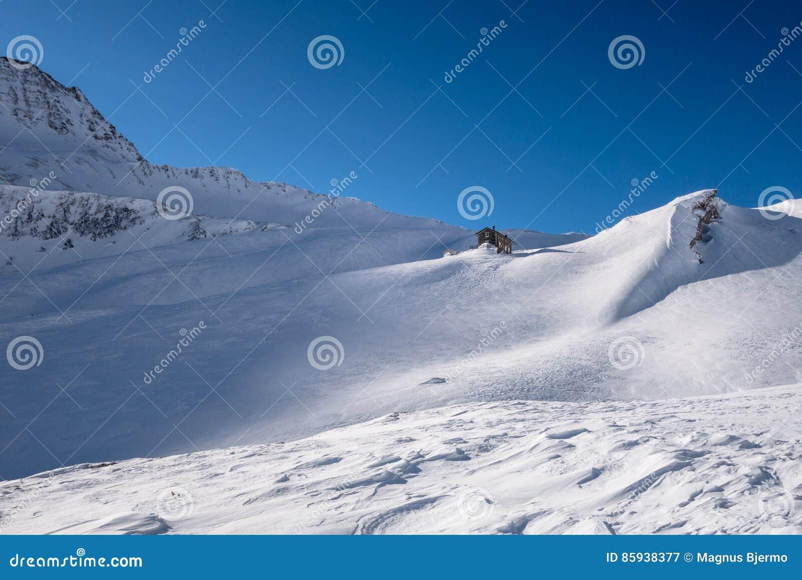 Αλπικό καταφύγιο κάτω από την κορυφογραμμή βουνών το χειμώνα στο ανεμοδαρμένο χιόνι