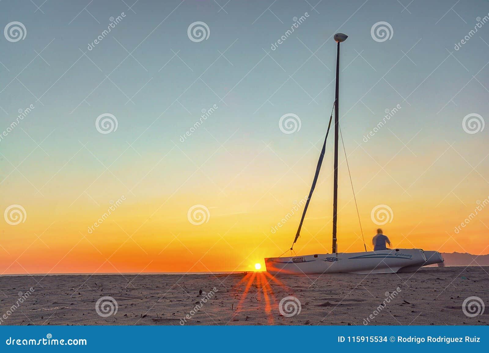 Βάρκα και ηλιοβασίλεμα πανιών στην παραλία
