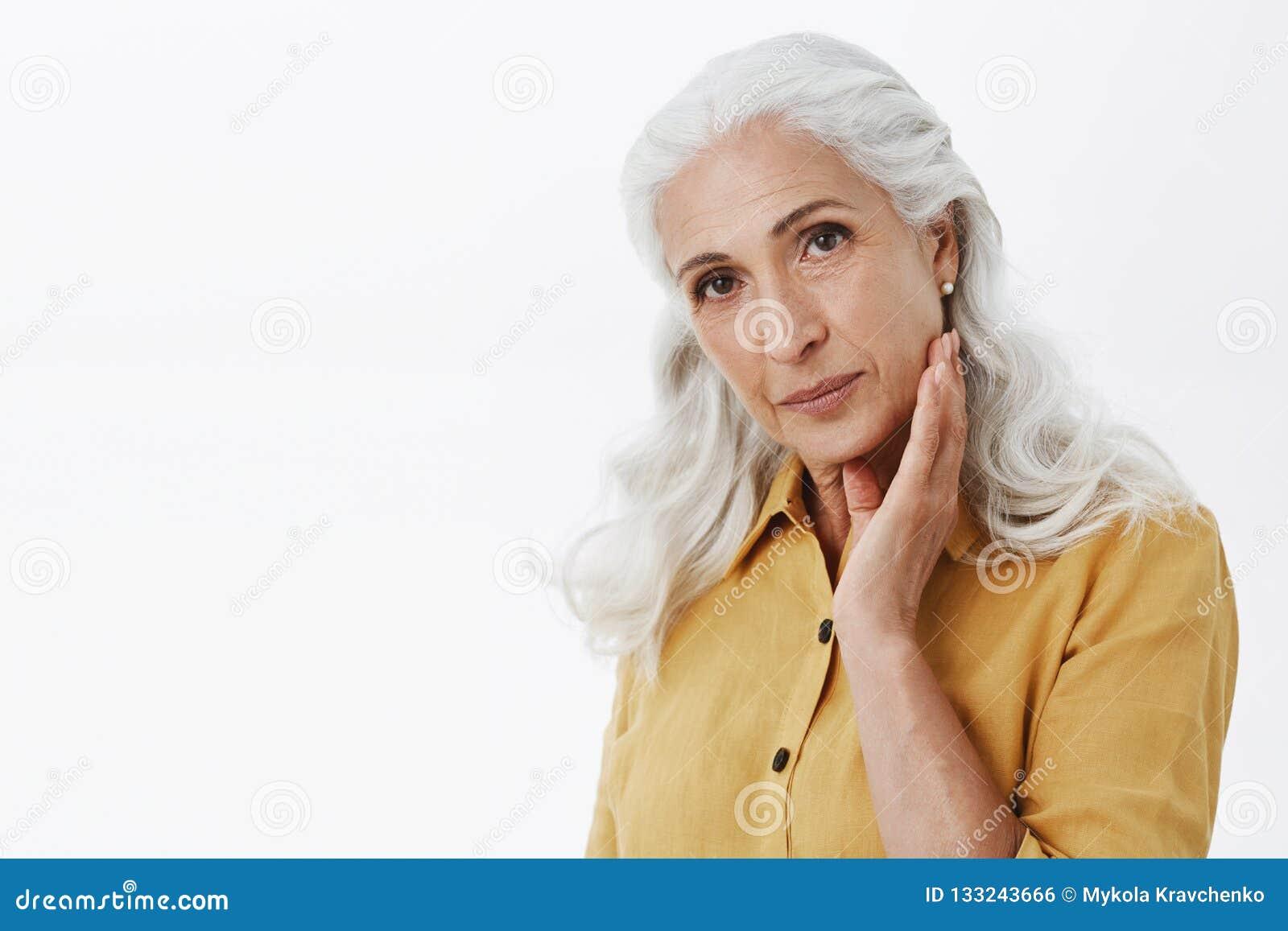 Βέβαια και θηλυκή κομψή ηλικιωμένη γυναίκα με τη μακριά άσπρη τρίχα στο μοντέρνο κίτρινο παλτό τάφρων σχετικά με το πρόσωπο ήπια