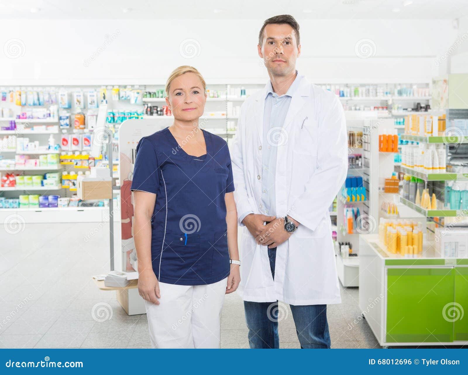 Βέβαιοι βοηθός και φαρμακοποιός που στέκονται στο φαρμακείο