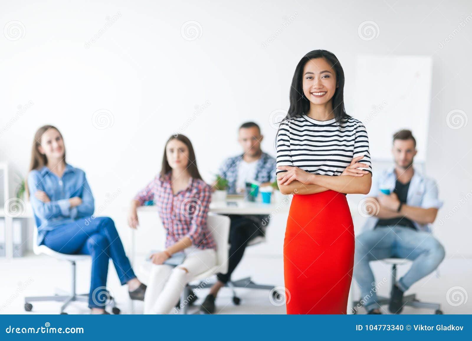 Βέβαιος ασιατικός επιχειρησιακός ηγέτης με την ομάδα της στο υπόβαθρο