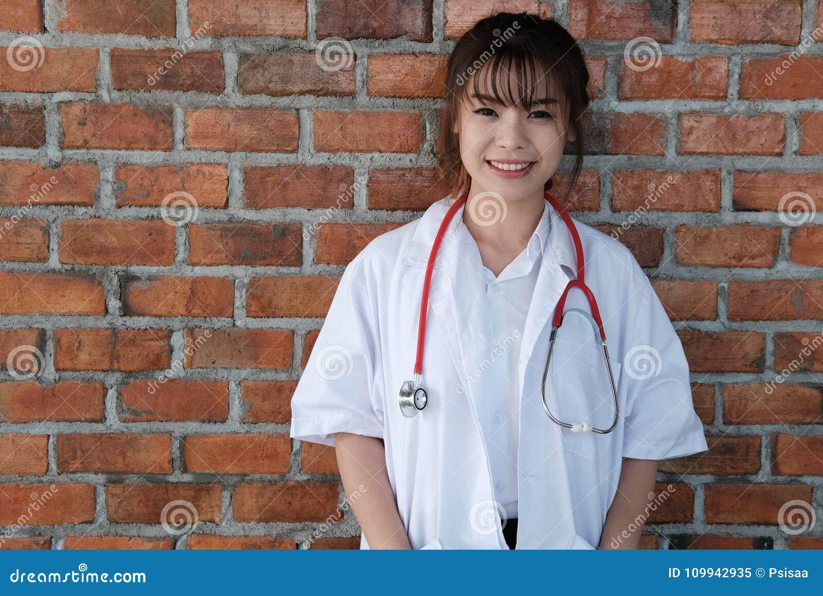 Βέβαιος νέος θηλυκός γιατρός που χαμογελά στη κάμερα Πορτρέτο του Μ