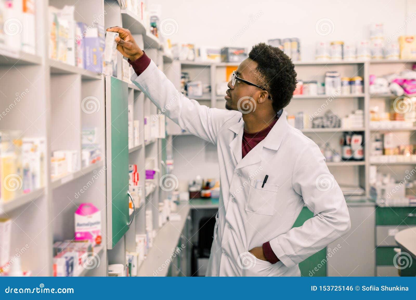 Βέβαιος φαρμακοποιός ατόμων αφροαμερικάνων που στέκεται στο εσωτερικό του φαρμακείου και που ψάχνει το φάρμακο στα ράφια στο φαρμ