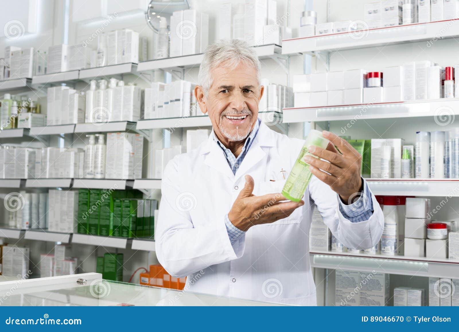 Βέβαιος φαρμακοποιός που χαμογελά ενώ προϊόν εκμετάλλευσης στο φαρμακείο