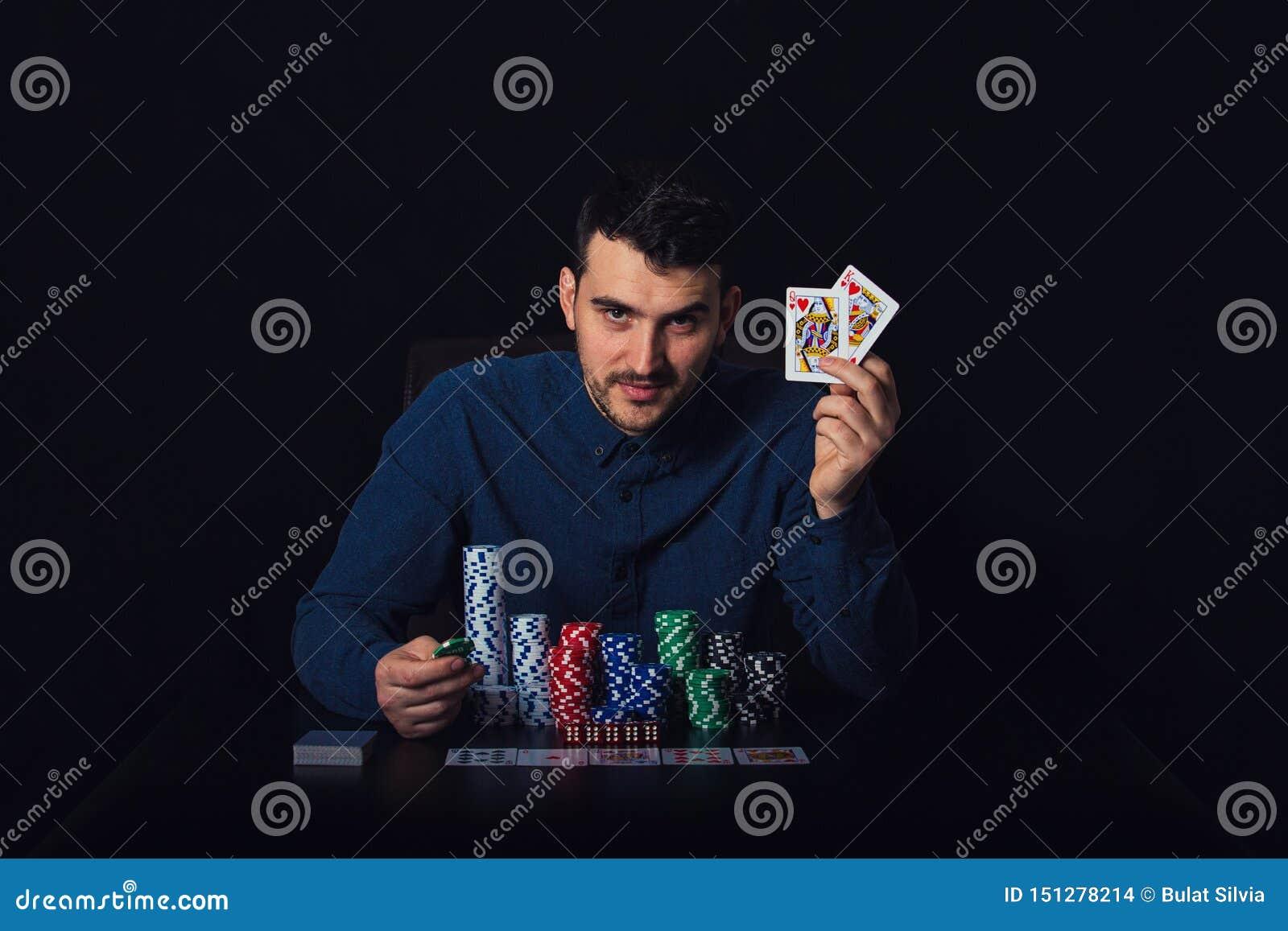 Βέβαιος φορέας πόκερ που κάθεται στον πίνακα χαρτοπαικτικών λεσχών που παρουσιάζει κερδίζοντας κάρτες του πέρα από το μαύρο υπόβα