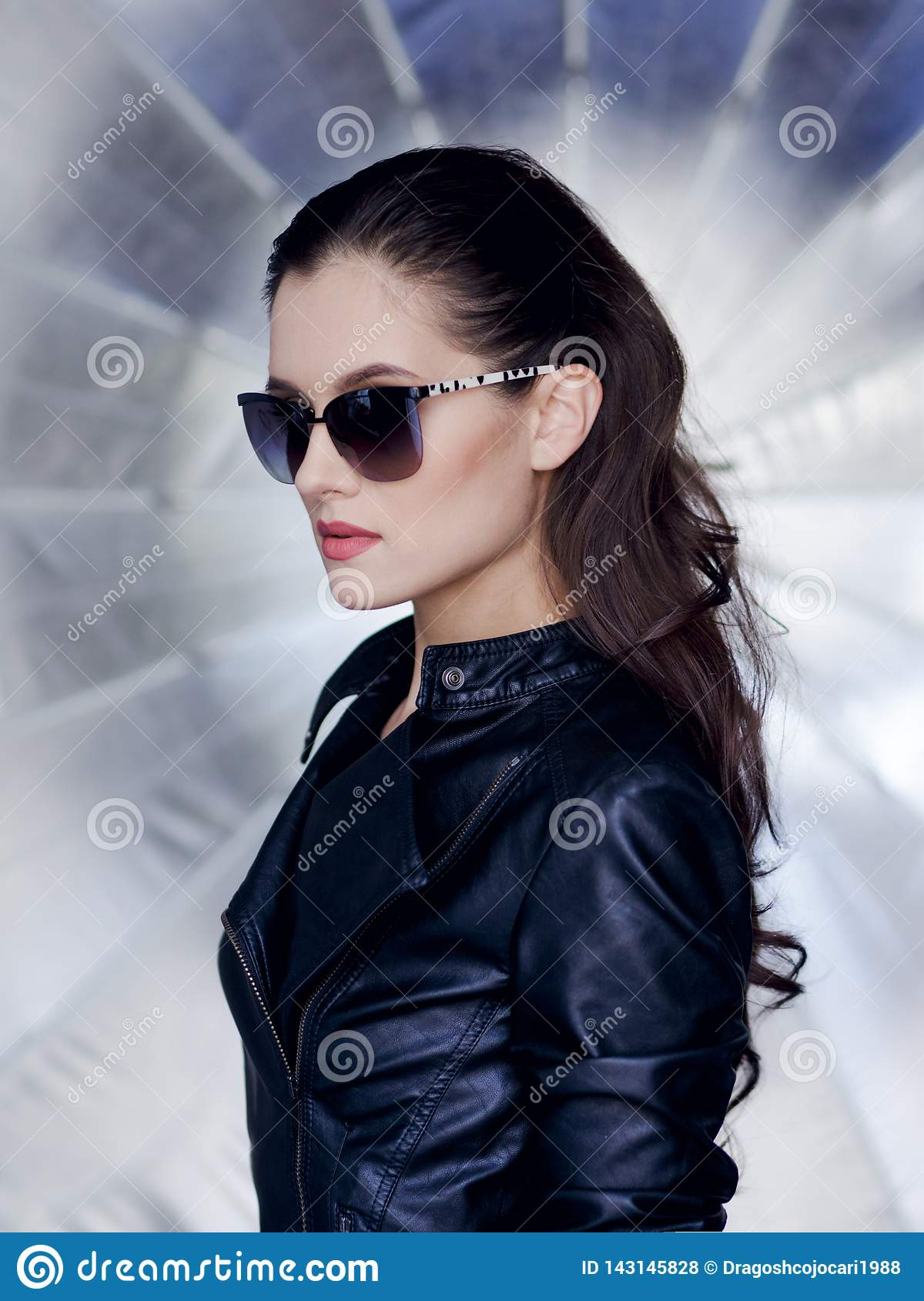 Βέβαιο και προκλητικό brunette με το όμορφο πρόσωπο, τα μοντέρνα γυαλιά ηλίου, το μαύρους σακάκι δέρματος και τον επαναστάτη hair