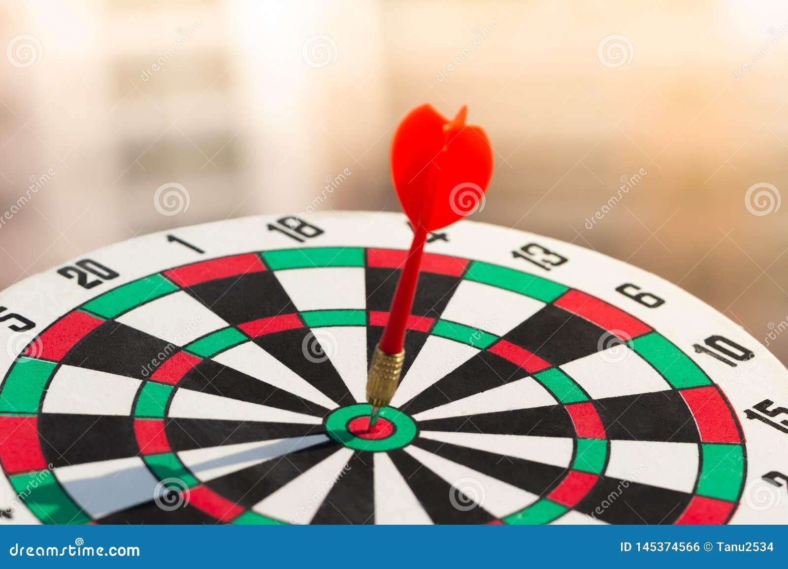 Βέλος βελών που χτυπά στο κέντρο στόχων του dartboard επιχειρησιακός στόχος έννοιας στην επιτυχία μάρκετινγκ