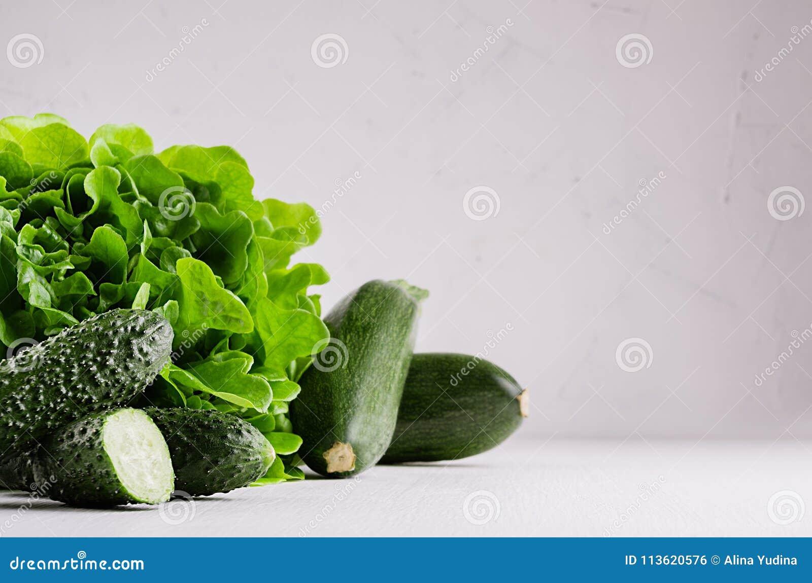 Βαθιά - πράσινα διαφορετικά λαχανικά στο μαλακό άσπρο ξύλινο πίνακα με το διάστημα αντιγράφων