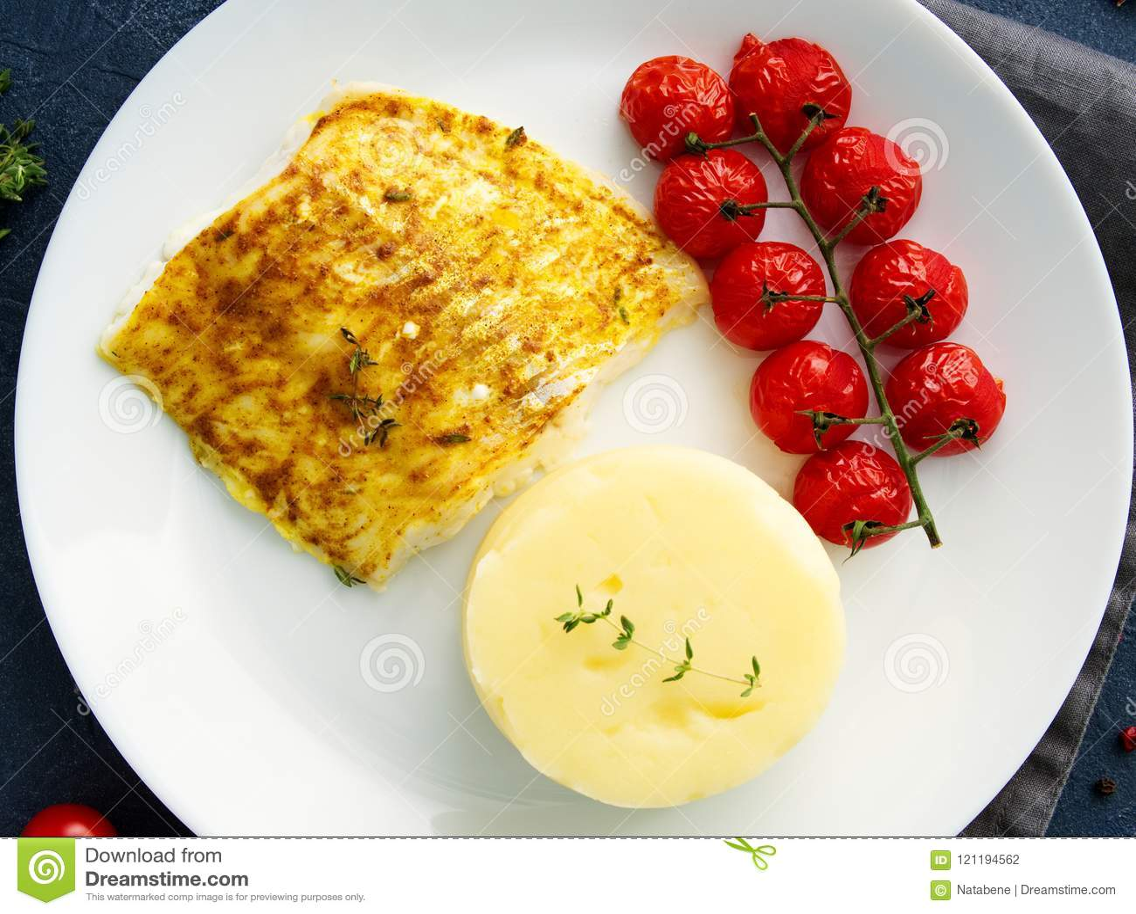 Βακαλάος ψαριών που ψήνεται στο φούρνο με τις πολτοποιηίδες πατάτες, ντομάτες, υγιή τρόφιμα διατροφής Σκούρο γκρι υπόβαθρο, τοπ ά