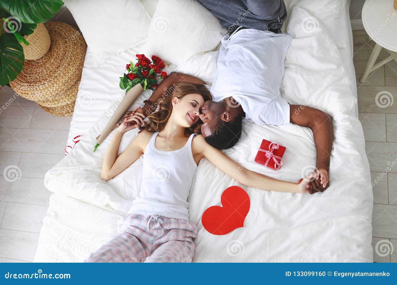 βαλεντίνος ημέρας s ευτυχές ζεύγος με τα λουλούδια στο κρεβάτι