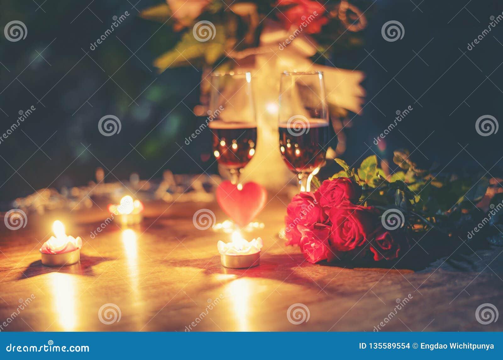 Βαλεντίνων ρομαντική επιτραπέζια ρύθμιση έννοιας αγάπης γευμάτων η ρομαντική διακόσμησε με το κόκκινο λουλούδι τριαντάφυλλων γυαλ