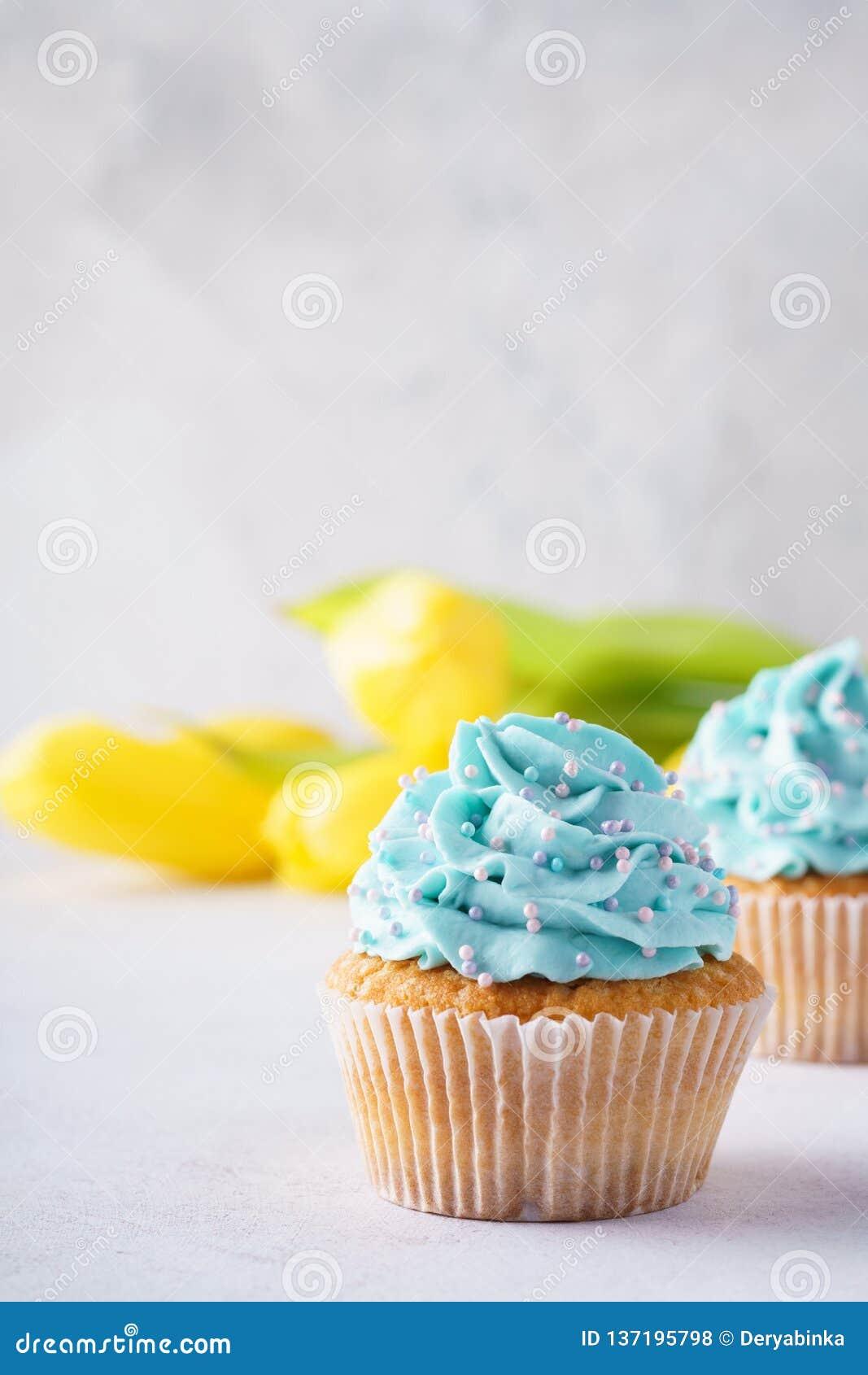 Βανίλια cupcakes με το μπλε πάγωμα και τα κίτρινα λουλούδια
