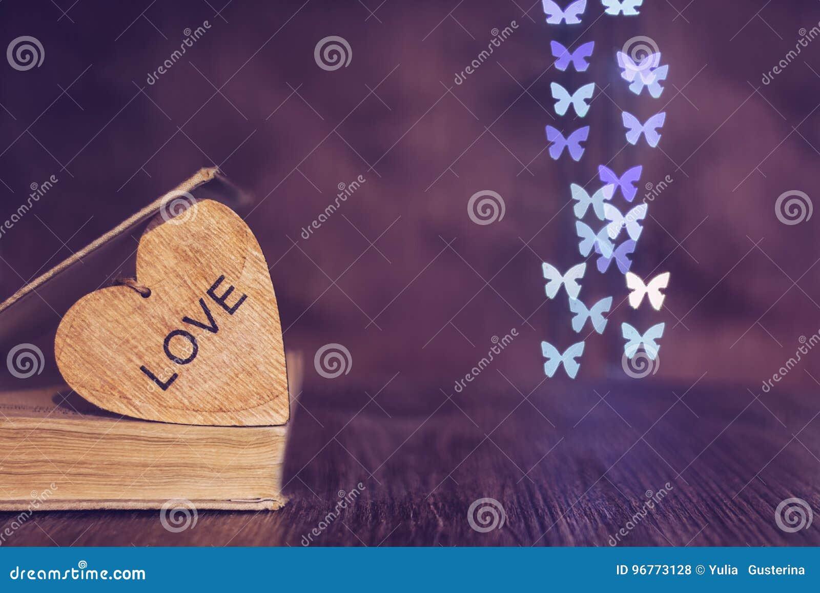 βαλεντίνος ημέρας s Βιβλίο καρδιών bokeh των πεταλούδων Ξύλινη καρδιά με την αγάπη λέξης