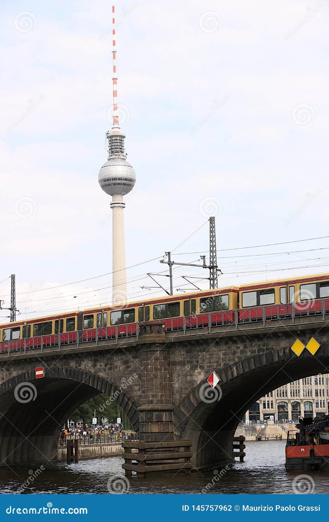 Βερολίνο, Γερμανία, στις 13 Ιουνίου 2018 Το τραίνο περνά πέρα από τη γέφυρα πετρών του ποταμού Στο υπόβαθρο μπορείτε να δείτε την