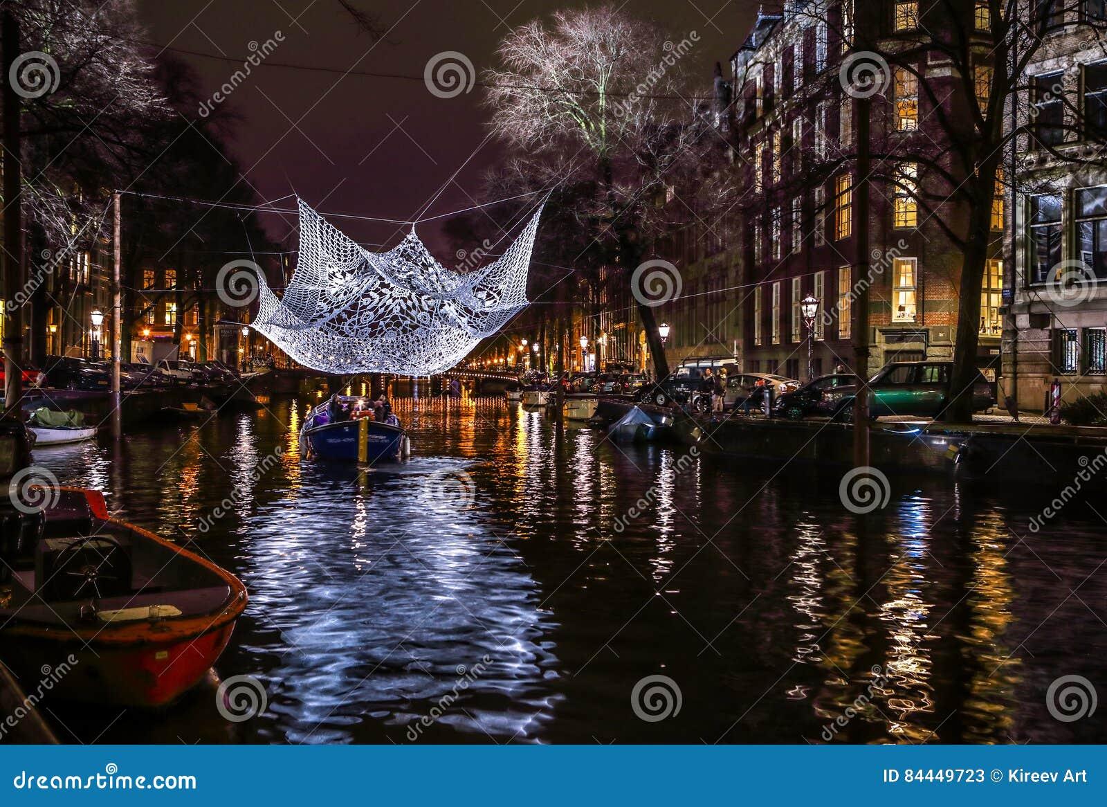 Βιασύνη βαρκών κρουαζιέρας στα κανάλια νύχτας Ελαφριές εγκαταστάσεις στα κανάλια νύχτας του Άμστερνταμ μέσα στο ελαφρύ φεστιβάλ