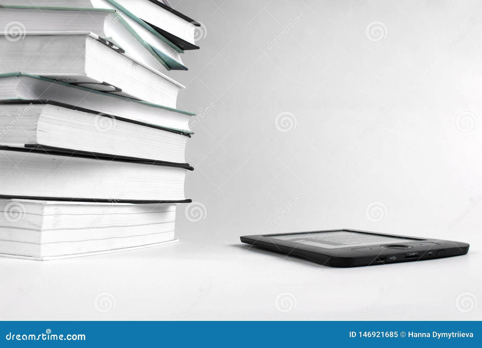 Βιβλία ανάγνωσης με ένα EBook Σωρός των βιβλίων και eBook στο άσπρο υπόβαθρο