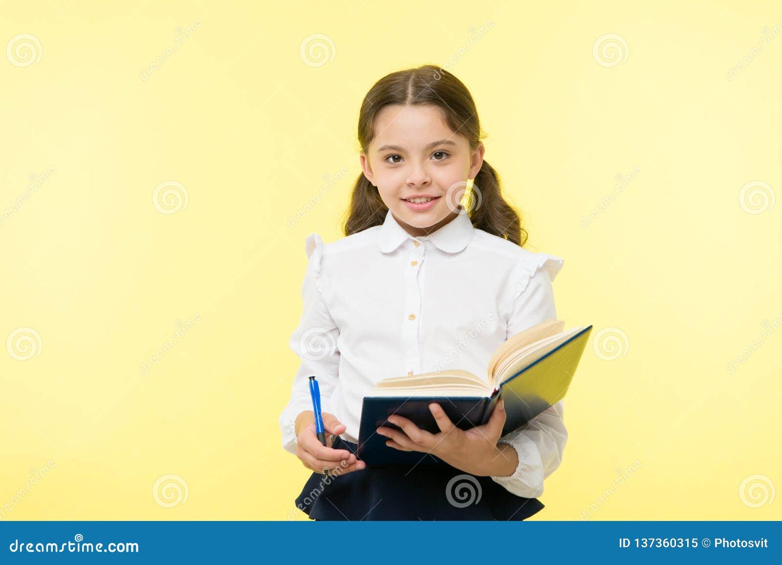 Βιβλίο και μάνδρα λαβής ενδυμάτων σχολικών στολών κοριτσιών παιδιών Το κορίτσι χαριτωμένο γράφει κάτω τις σημειώσεις ιδέας Σημειώ