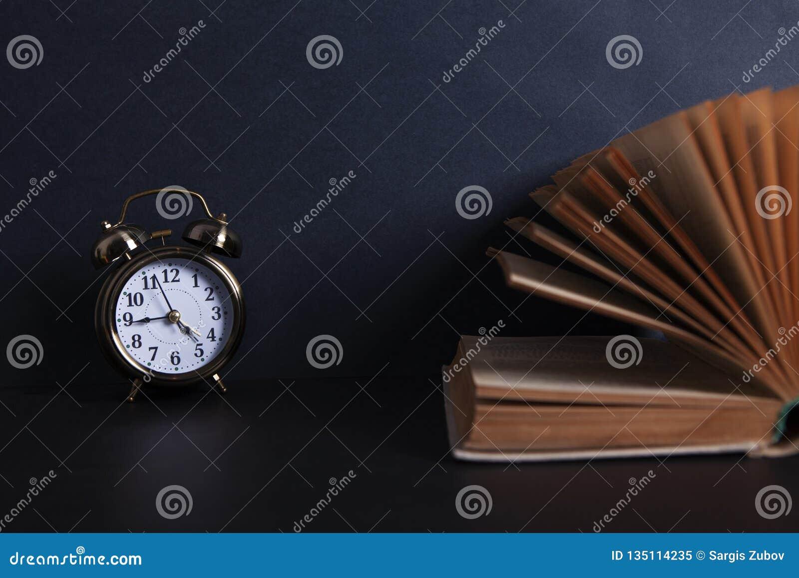 Βιβλίο και ξυπνητήρι στον υπολογιστή γραφείου