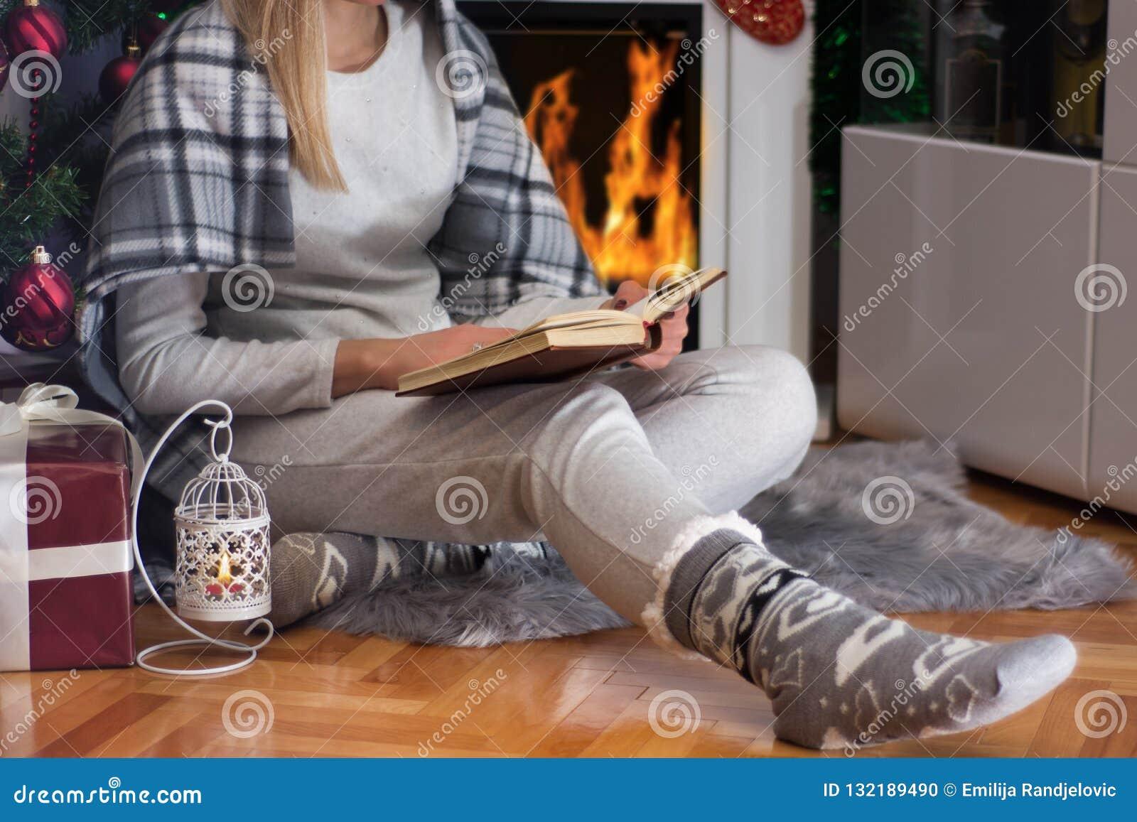Βιβλίο και συνεδρίαση ανάγνωσης κοριτσιών στο πάτωμα κοντά στην εστία