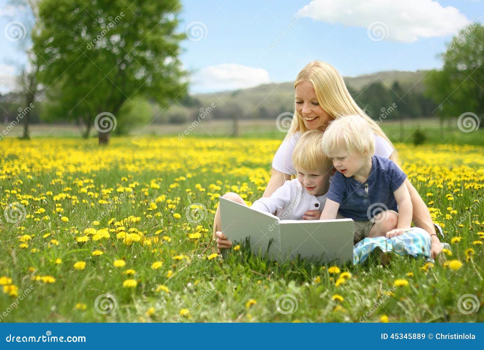 Βιβλίο ιστορίας ανάγνωσης μητέρων σε δύο μικρά παιδιά έξω σε Meado