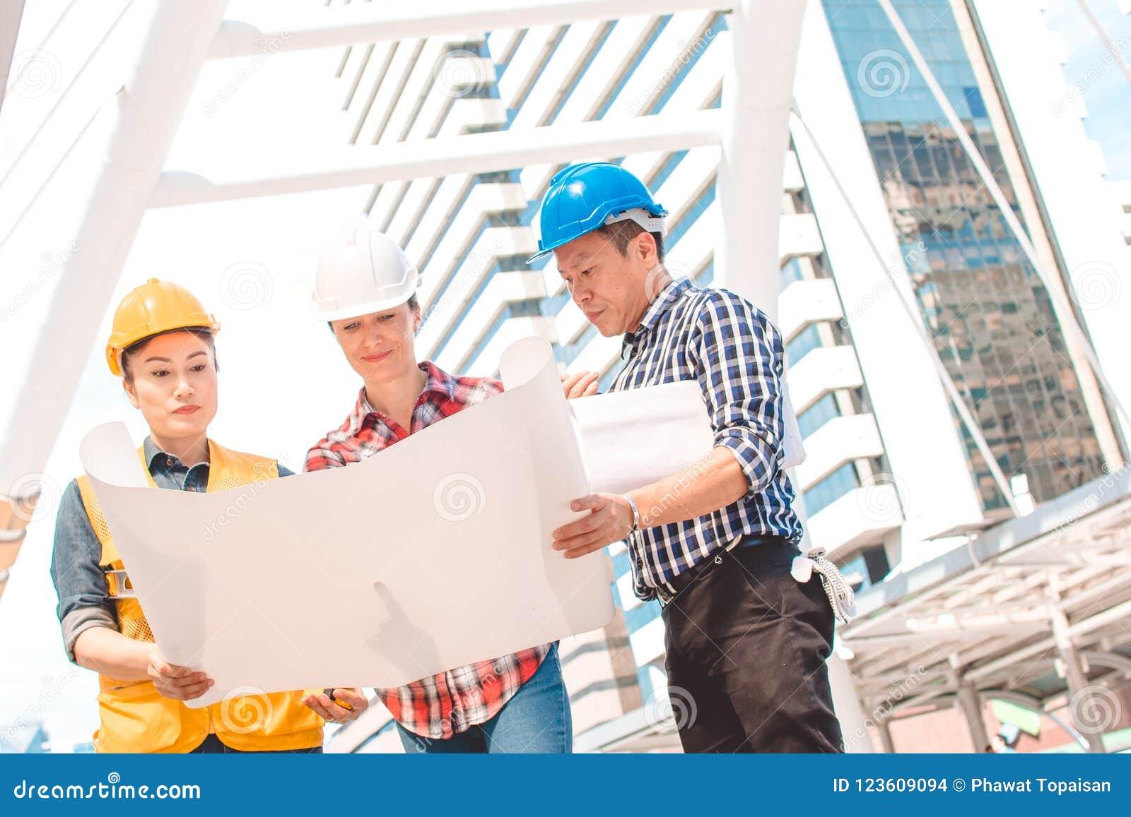 Βιομηχανική εφαρμοσμένη μηχανική κρανών ασφάλειας ένδυσης μηχανικών τρία που λειτουργεί και που μιλά με την επιθεώρηση σχεδίων