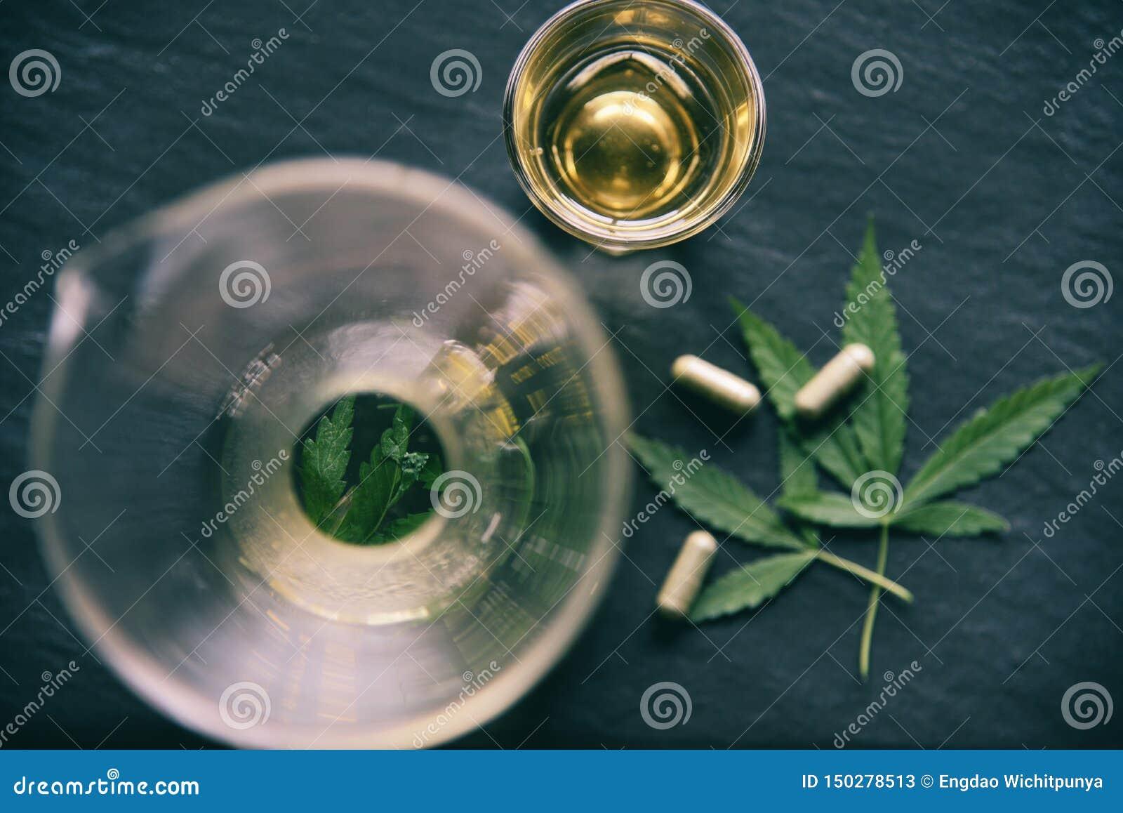 Βοτανικές τσάι και κάψα καννάβεων φυτών φύλλων μαριχουάνα στα σκοτεινά φύλλα υποβάθρου/κάνναβης για την ιατρική υγειονομική περίθ