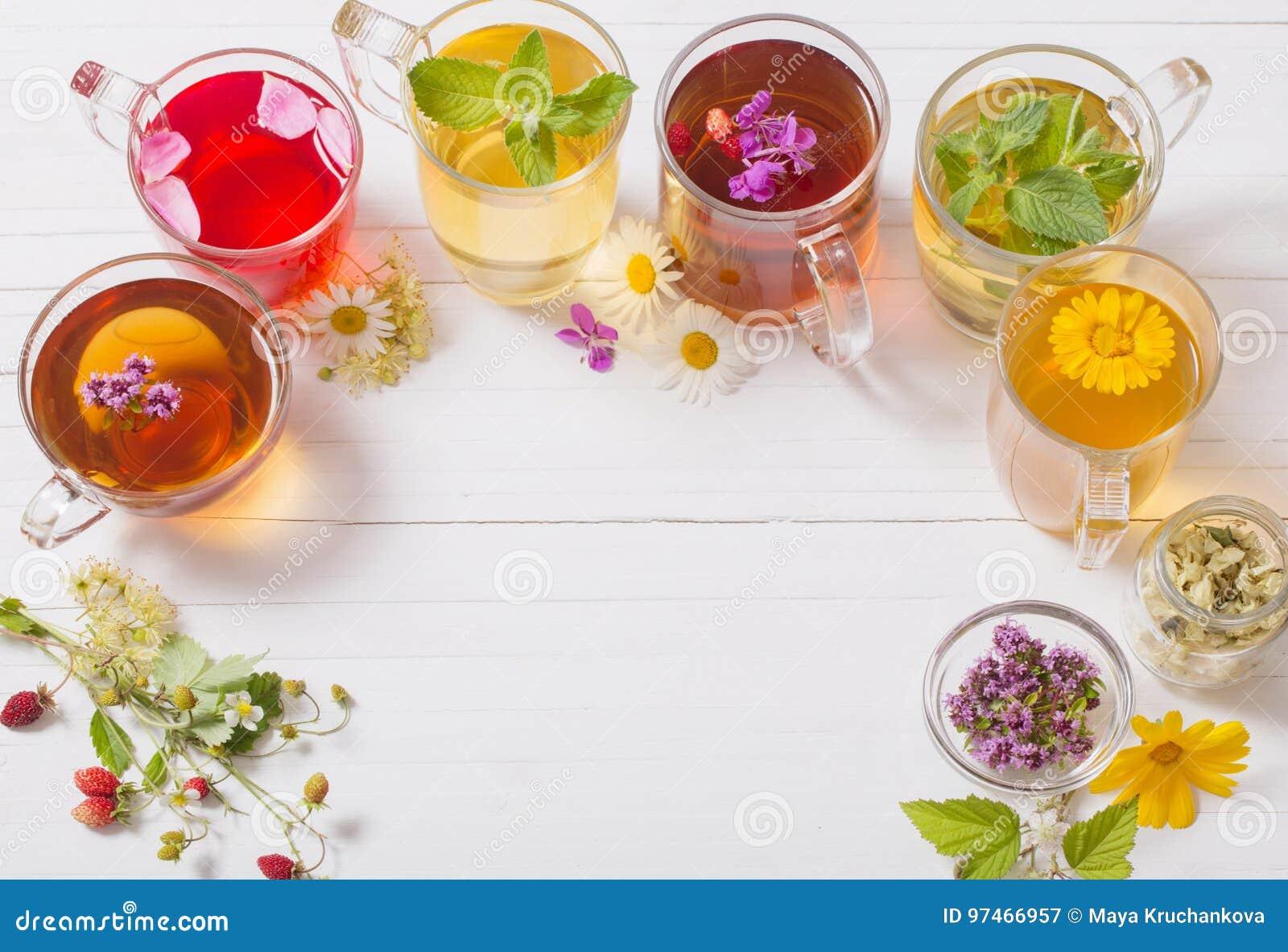 Βοτανικό τσάι στα φλυτζάνια στο άσπρο υπόβαθρο