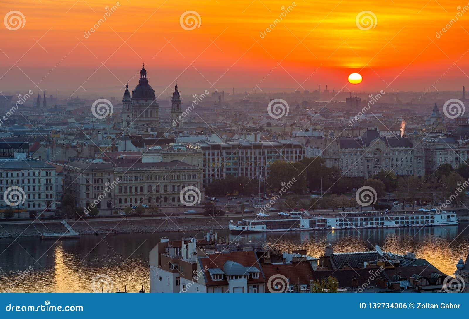 Βουδαπέστη, Ουγγαρία - όμορφη χρυσή ανατολή πέρα από τη Βουδαπέστη με Basilca του ST Stephen, κρουαζιερόπλοιο στον ποταμό Δούναβη