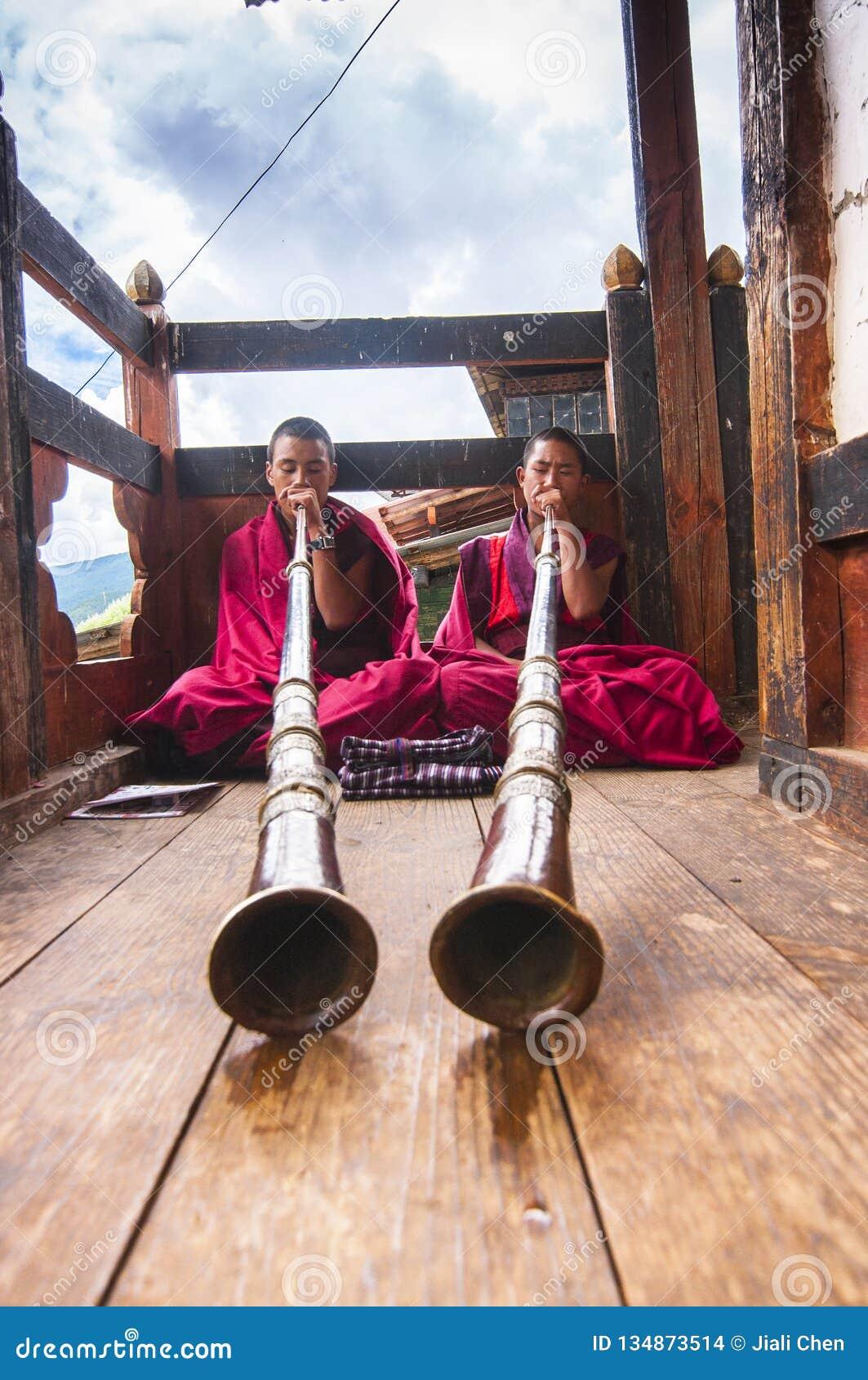 Βουδιστικοί μοναχοί που παίζουν τα θιβετιανά κέρατα, κοιλάδα Bumthang, Μπουτάν