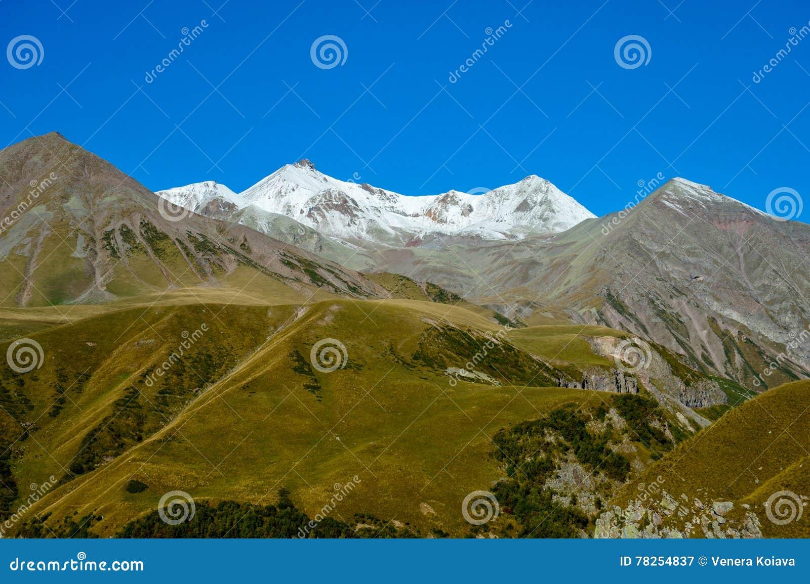 Βουνά Καύκασου κατά μέγιστη άποψη θερινού τη χιονώδη Mkinvari από Gudauri