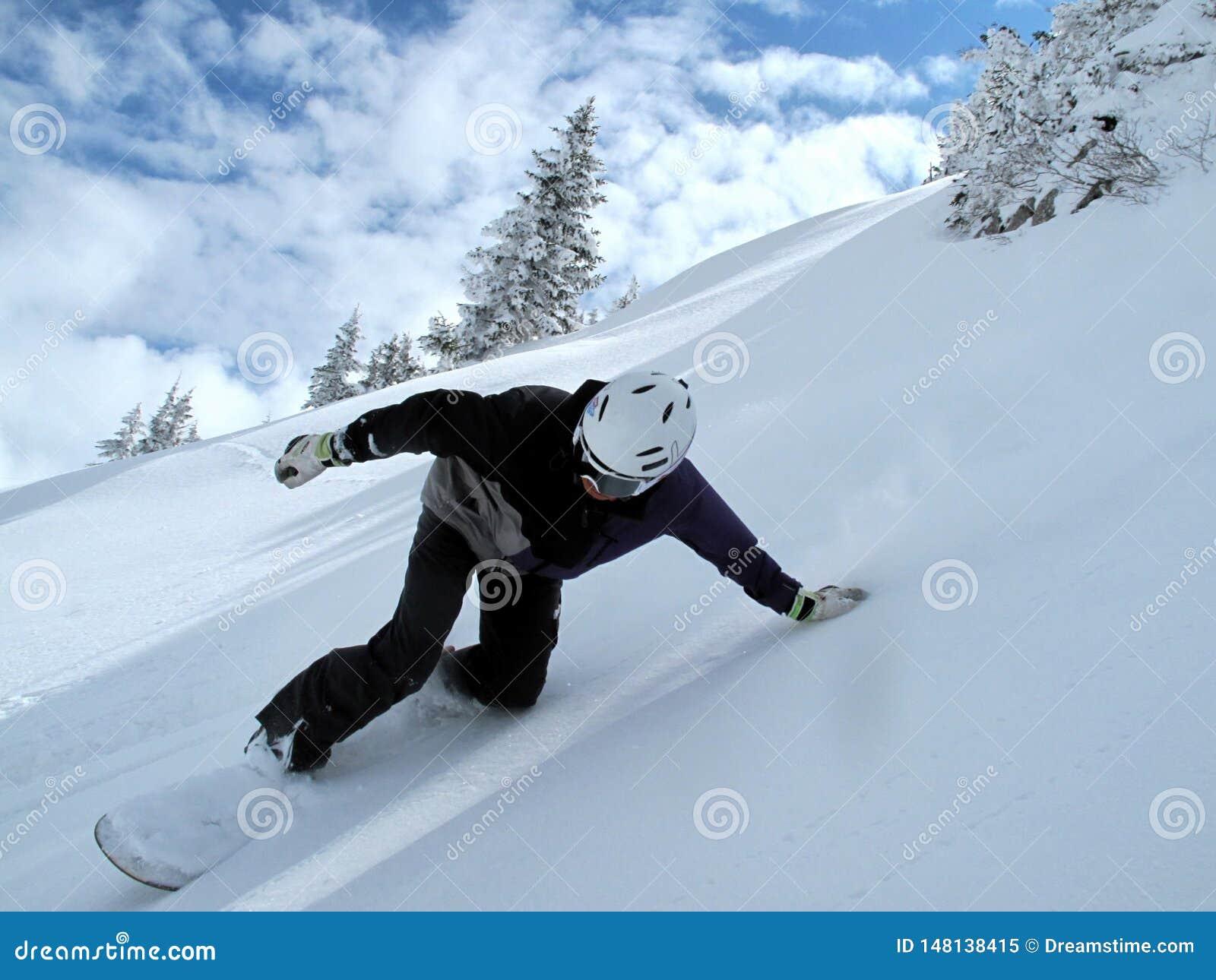 Βουνό με τα σύννεφα και το χιόνι, snowboarder στην πλήρη ταχύτητα