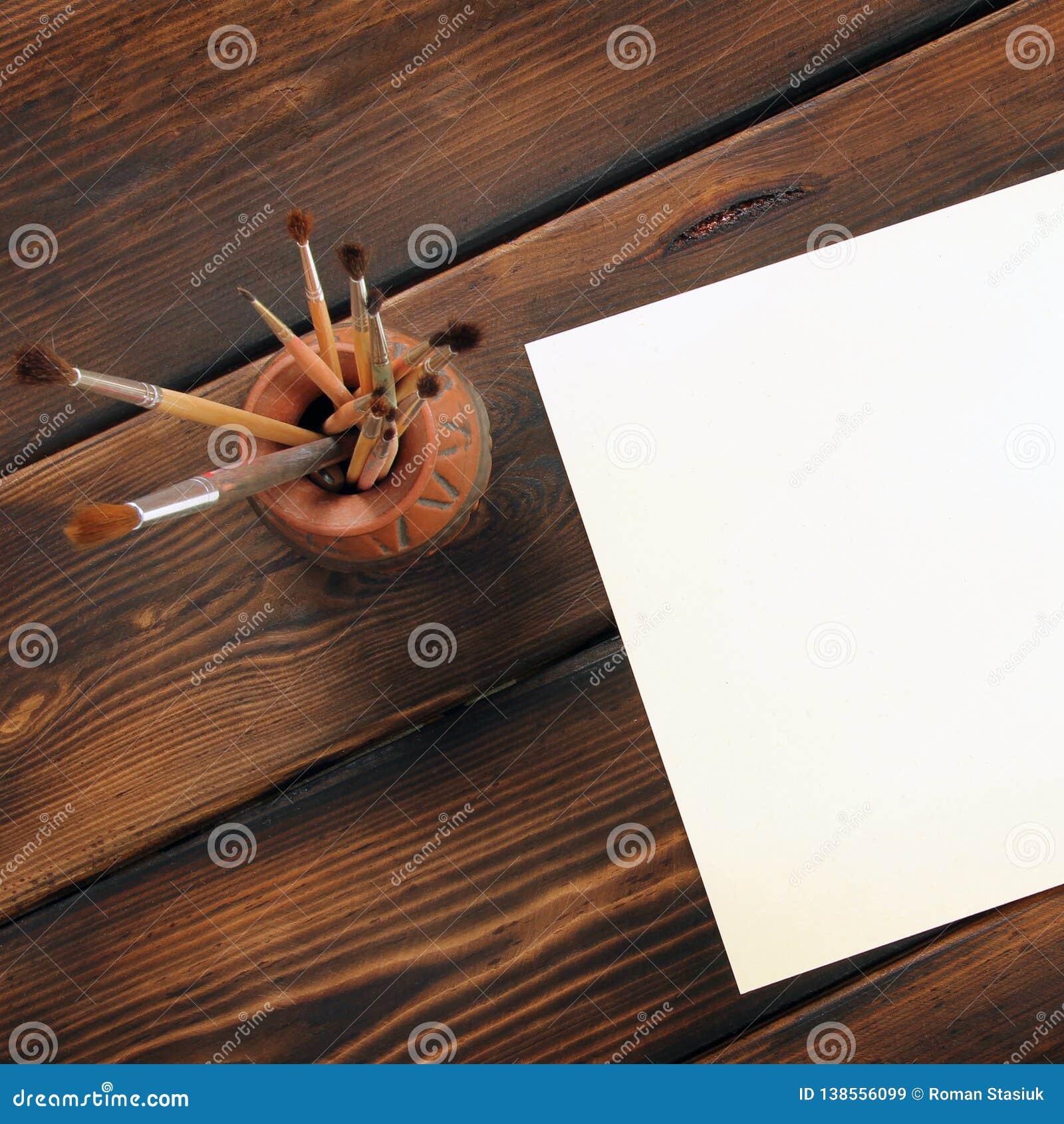 Βούρτσες και έγγραφο χρωμάτων για το ξύλινο υπόβαθρο