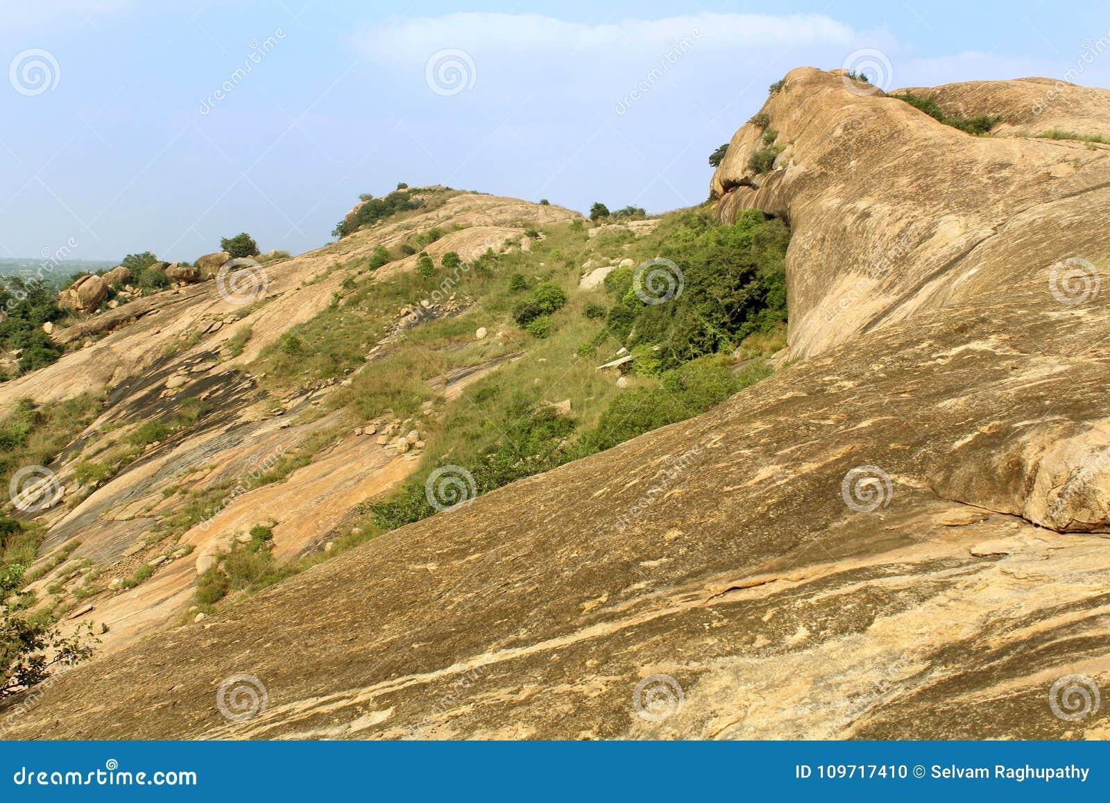 Βράχοι με το τοπίο λόφων ουρανού sittanavasal