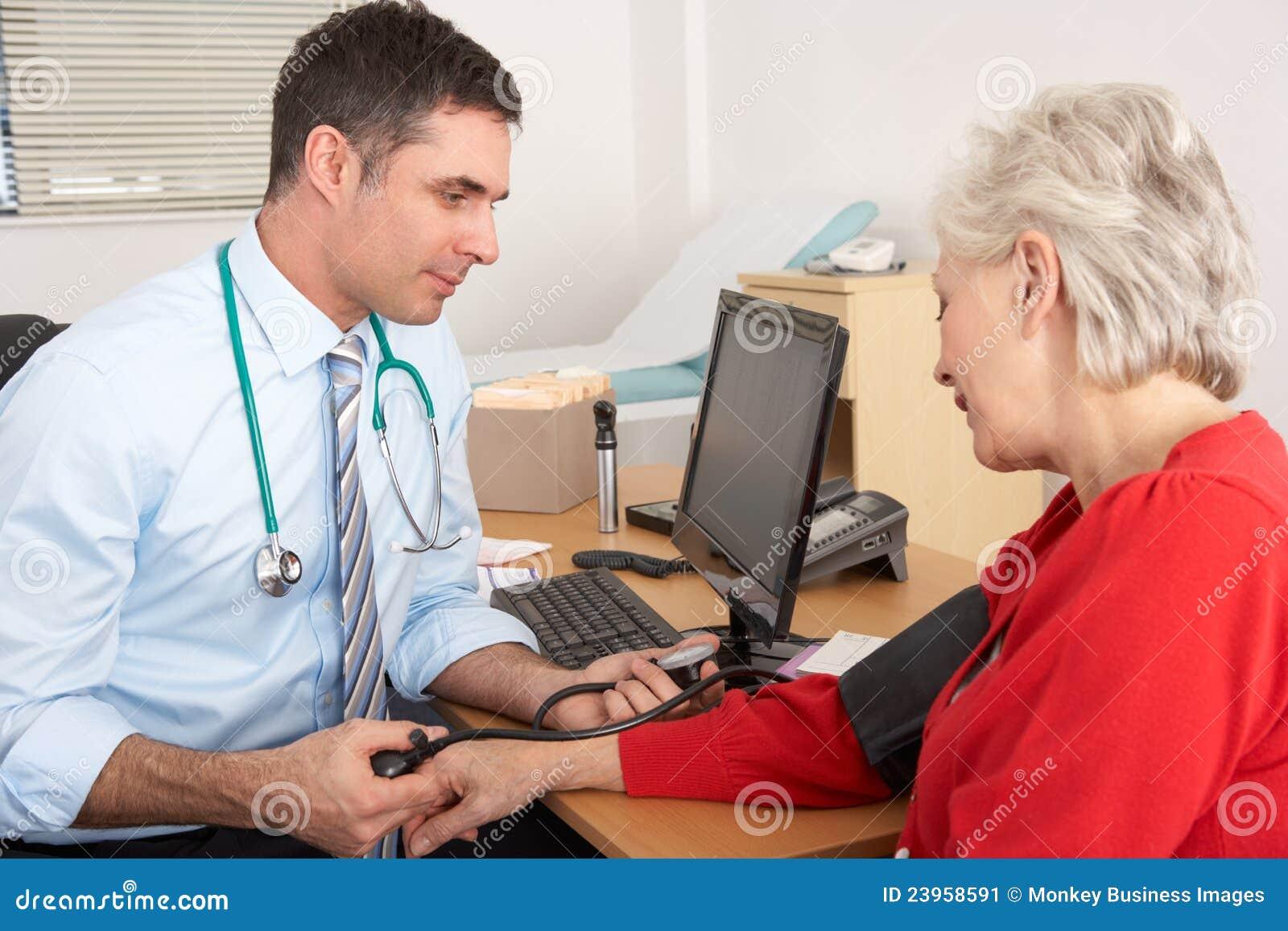 Βρετανικός γιατρός που παίρνει τη πίεση του αίματος της ανώτερης γυναίκας
