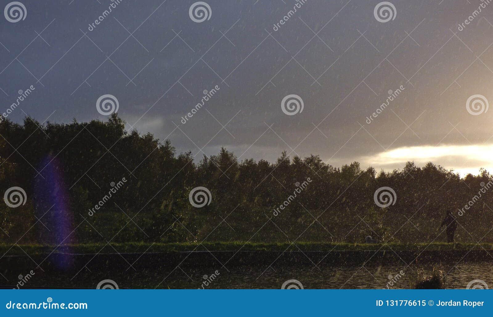 Βροχερό απόγευμα - η βροχή άρχισε κάτω δίπλα στο κανάλι με τον ήλιο που λάμπει στην απόσταση, φωτογραφία που λήφθηκε στο UK