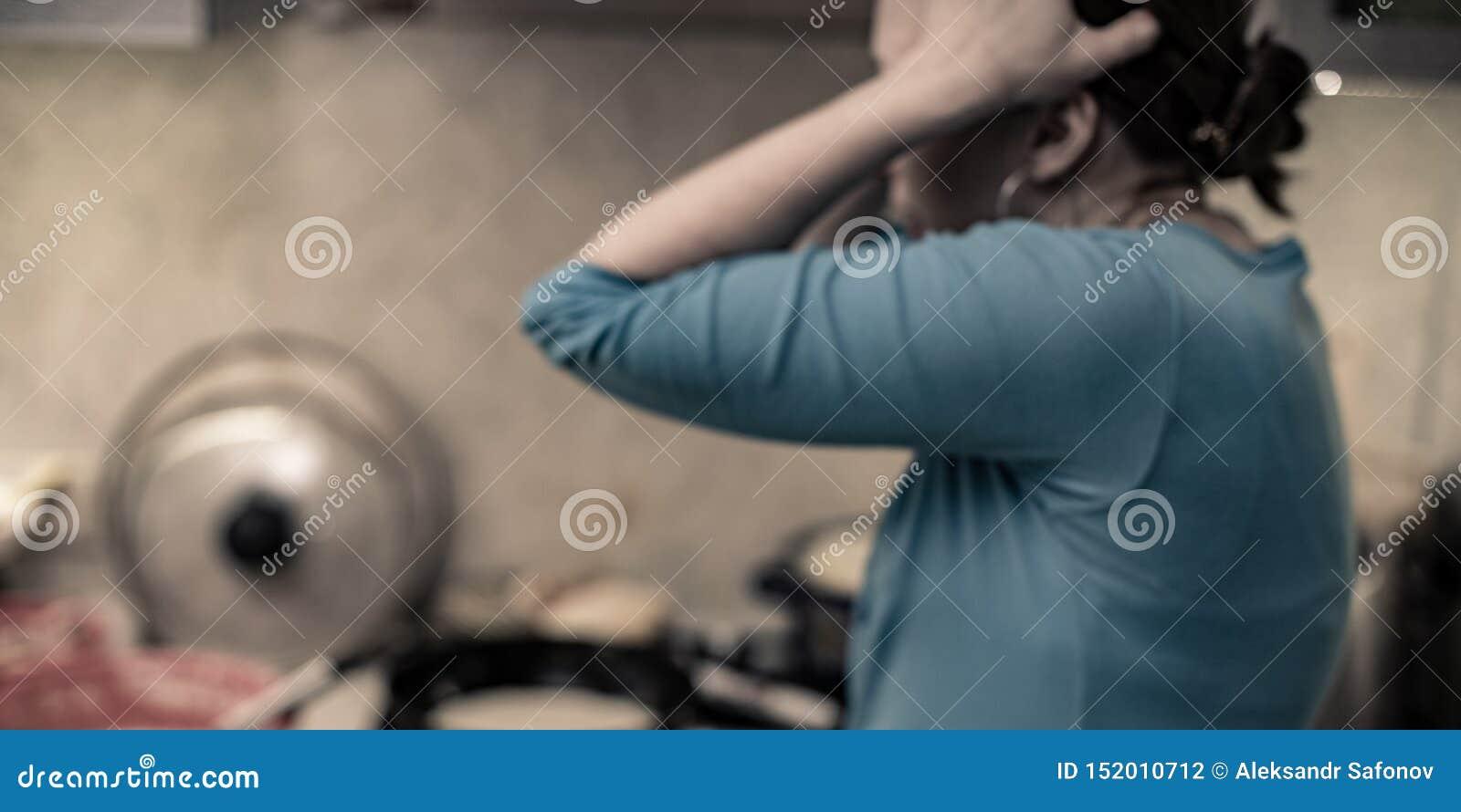 Βρωμίστε στην κουζίνα που μια γυναίκα κρατά το κεφάλι της στη φρίκη από το χάος