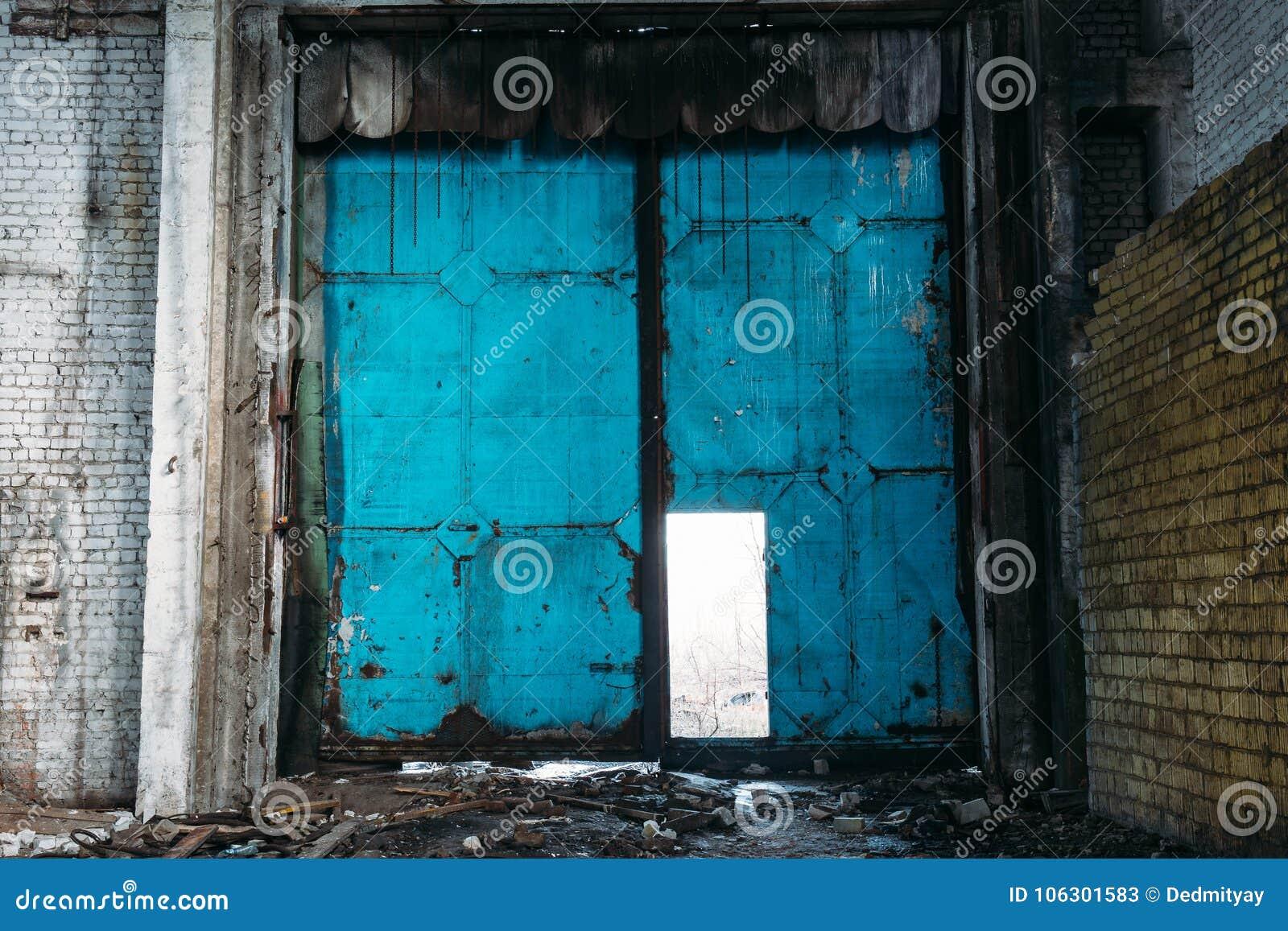 Βρώμικη πόρτα χάλυβα στην εγκαταλειμμένη αποθήκη εμπορευμάτων Πύλη γκαράζ ή αποθήκευσης εργοστασίων