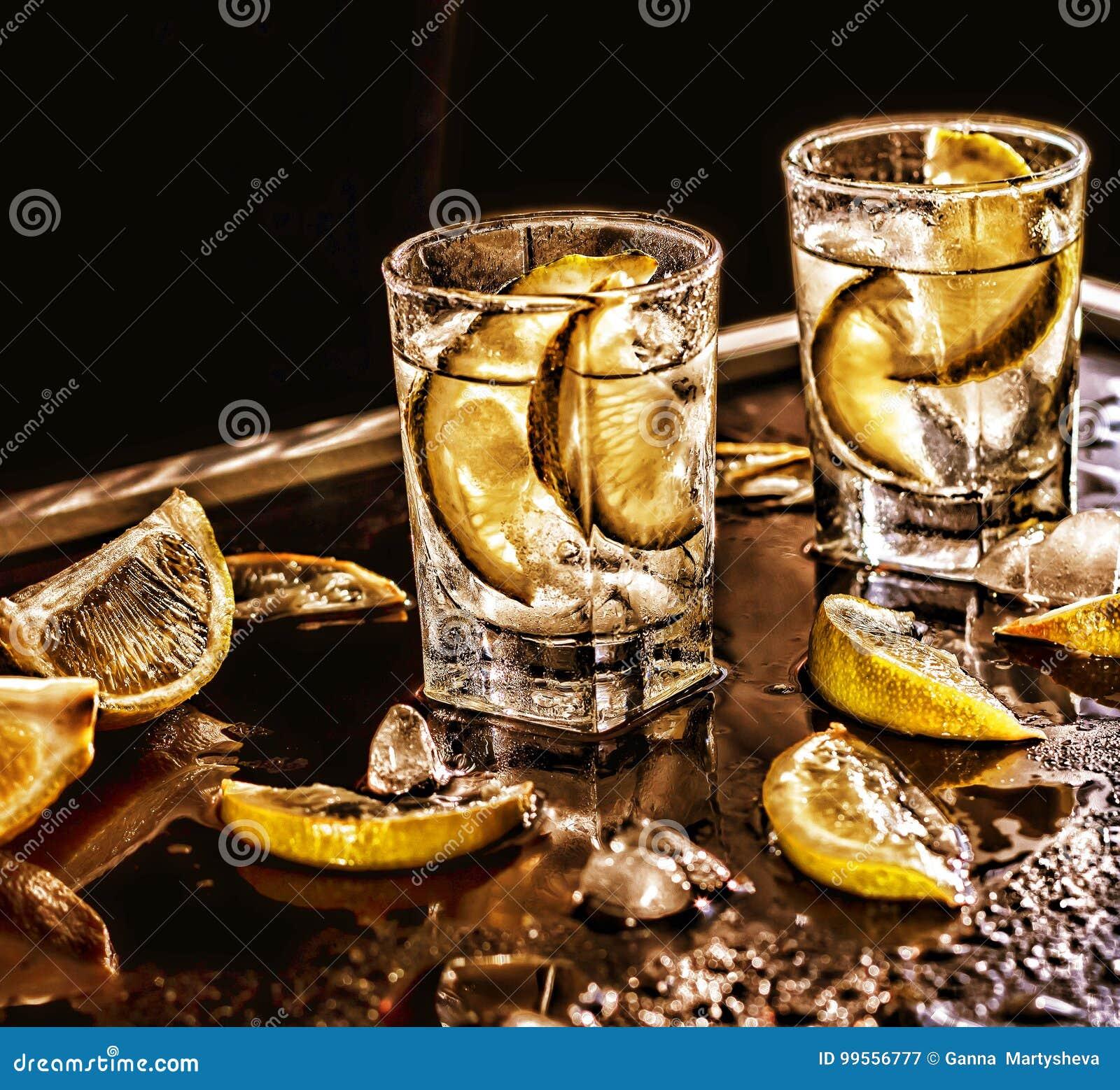 Βότκα κινηματογραφήσεων σε πρώτο πλάνο σε ένα γυαλί με τον πάγο, βότκα ασβέστη, τζιν, τονωτικό, tequila