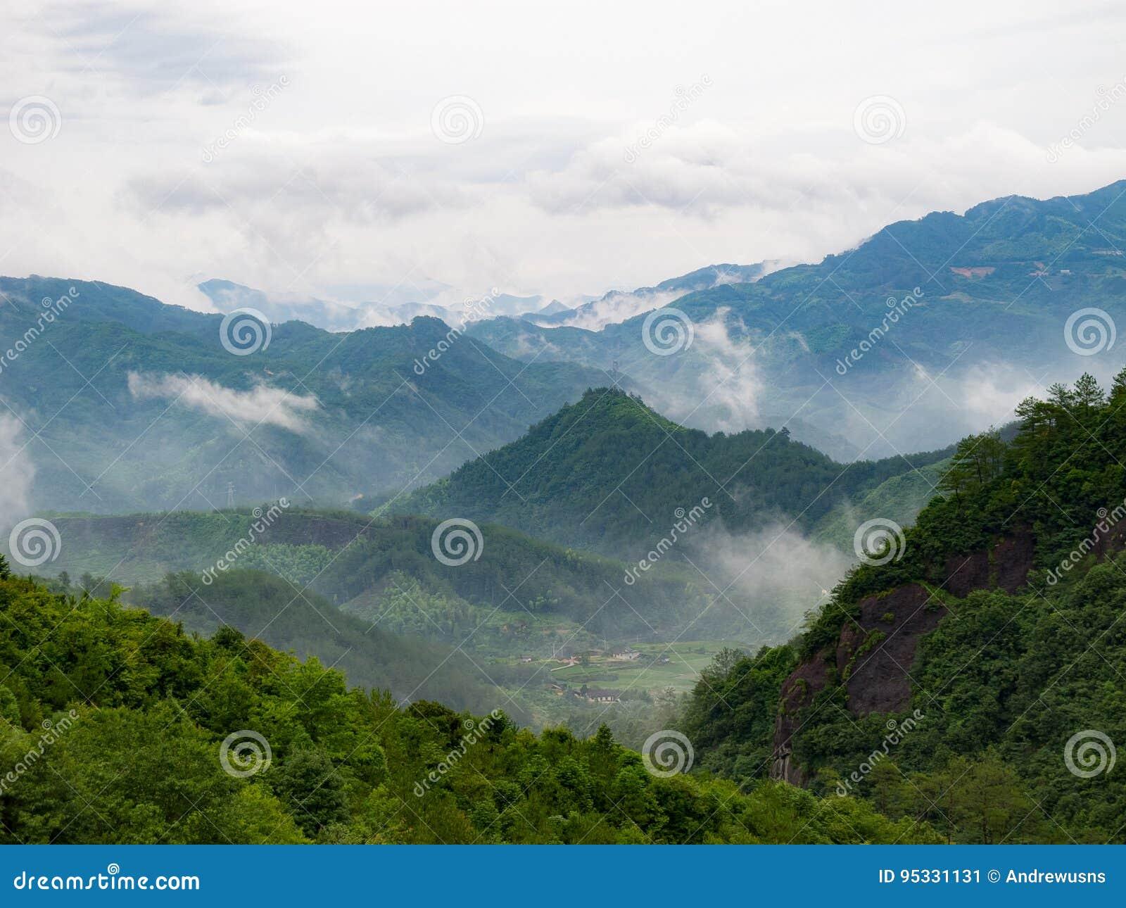Βλέπω? χωριό thorugh σύννεφα γύρω από το βουνό