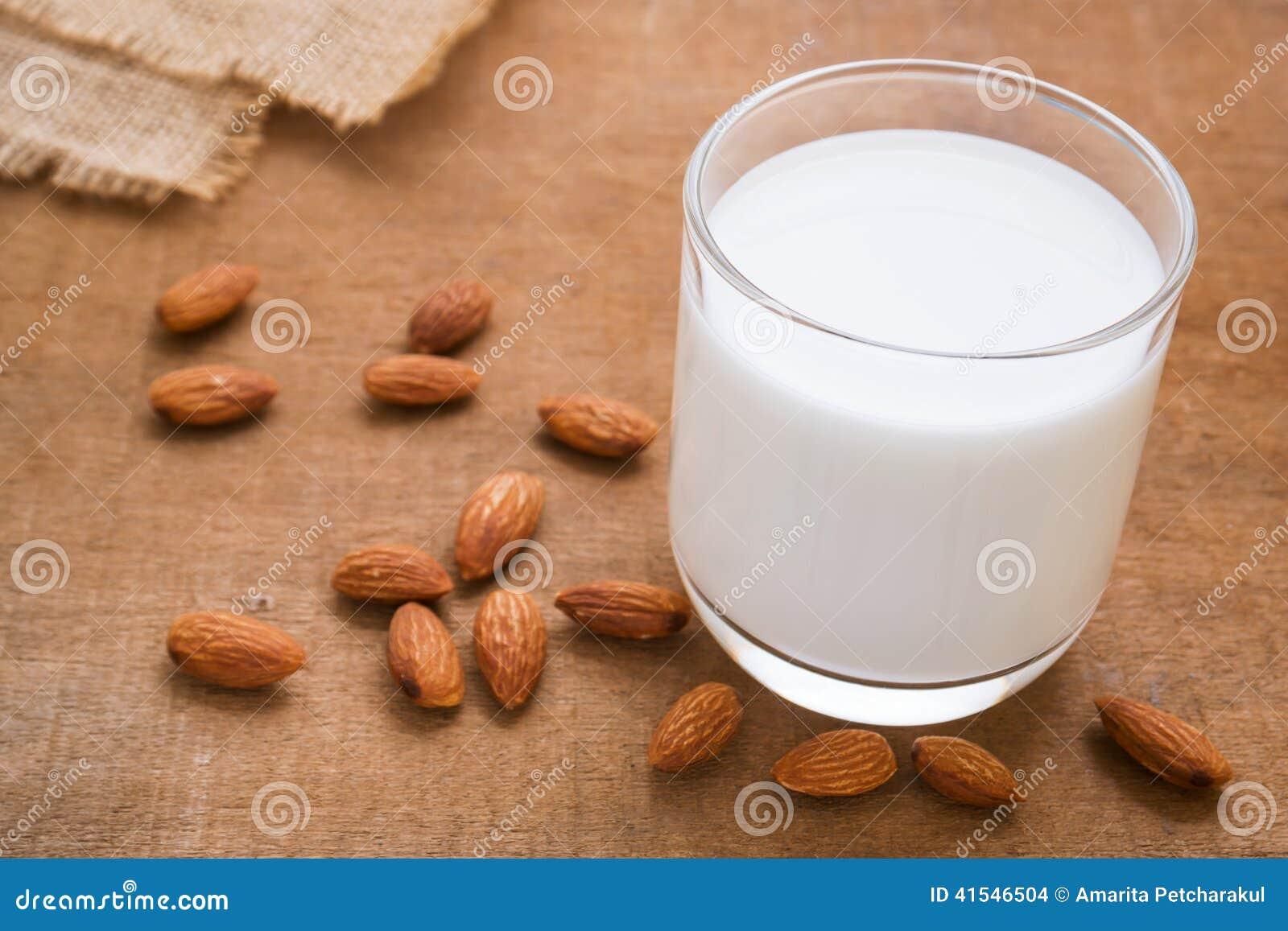 Γάλα αμυγδάλων και αμύγδαλο στον ξύλινο πίνακα