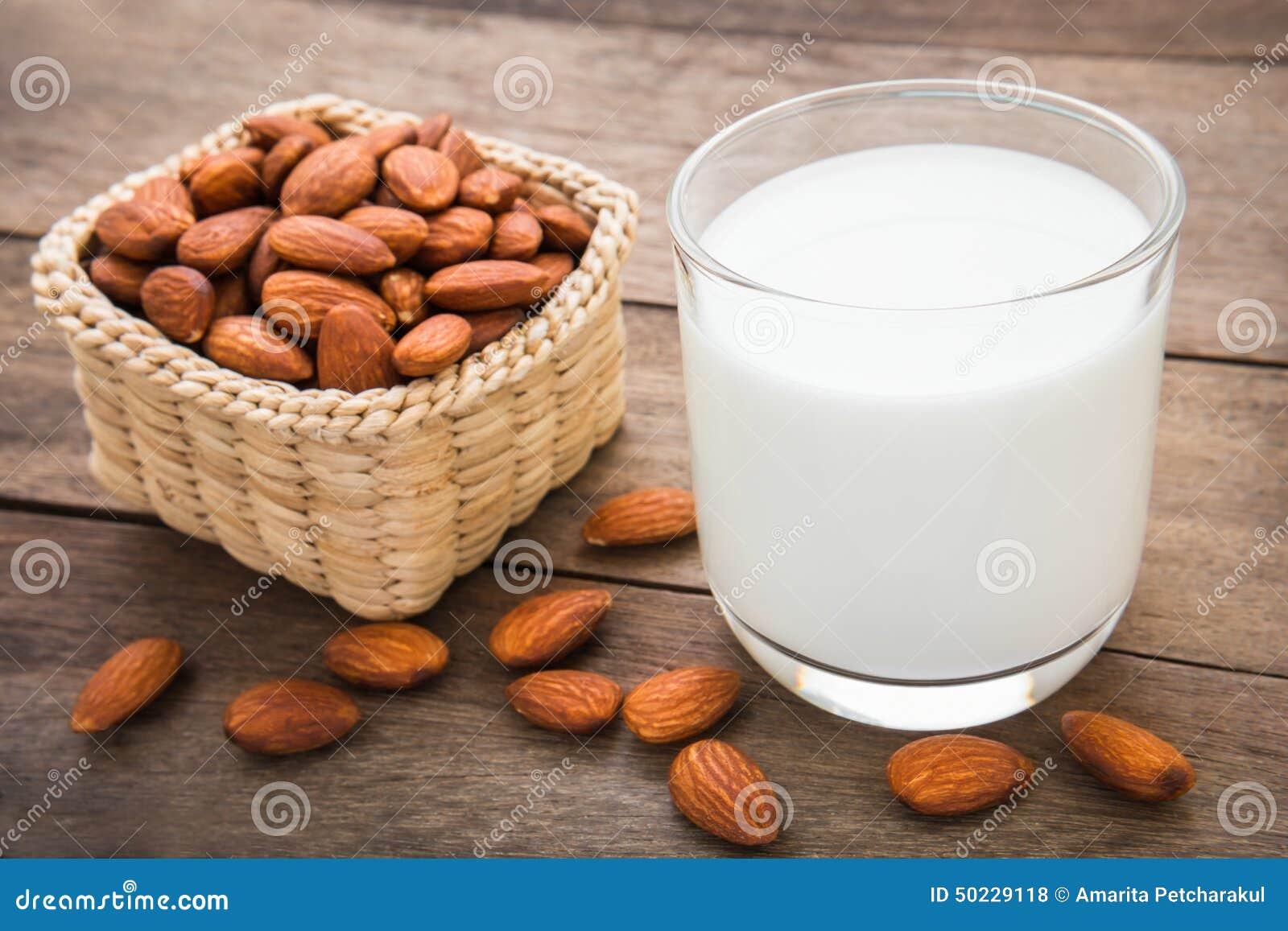 Γάλα αμυγδάλων στο γυαλί με τα αμύγδαλα στον ξύλινο πίνακα