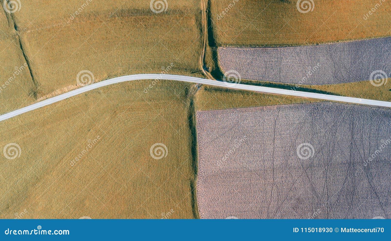 Γήινη ` s γραμμή Μια κάθετη προοπτική κηφήνων των επίγειων ` s χρωμάτων και των μορφών γεωργικά πεδία