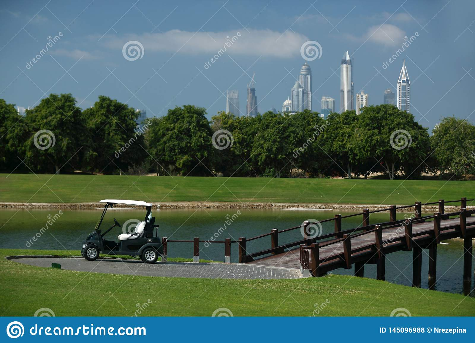 γήπεδο του γκολφ στο Ντουμπάι με τους φοίνικες και ουρανοξύστες στο υπ