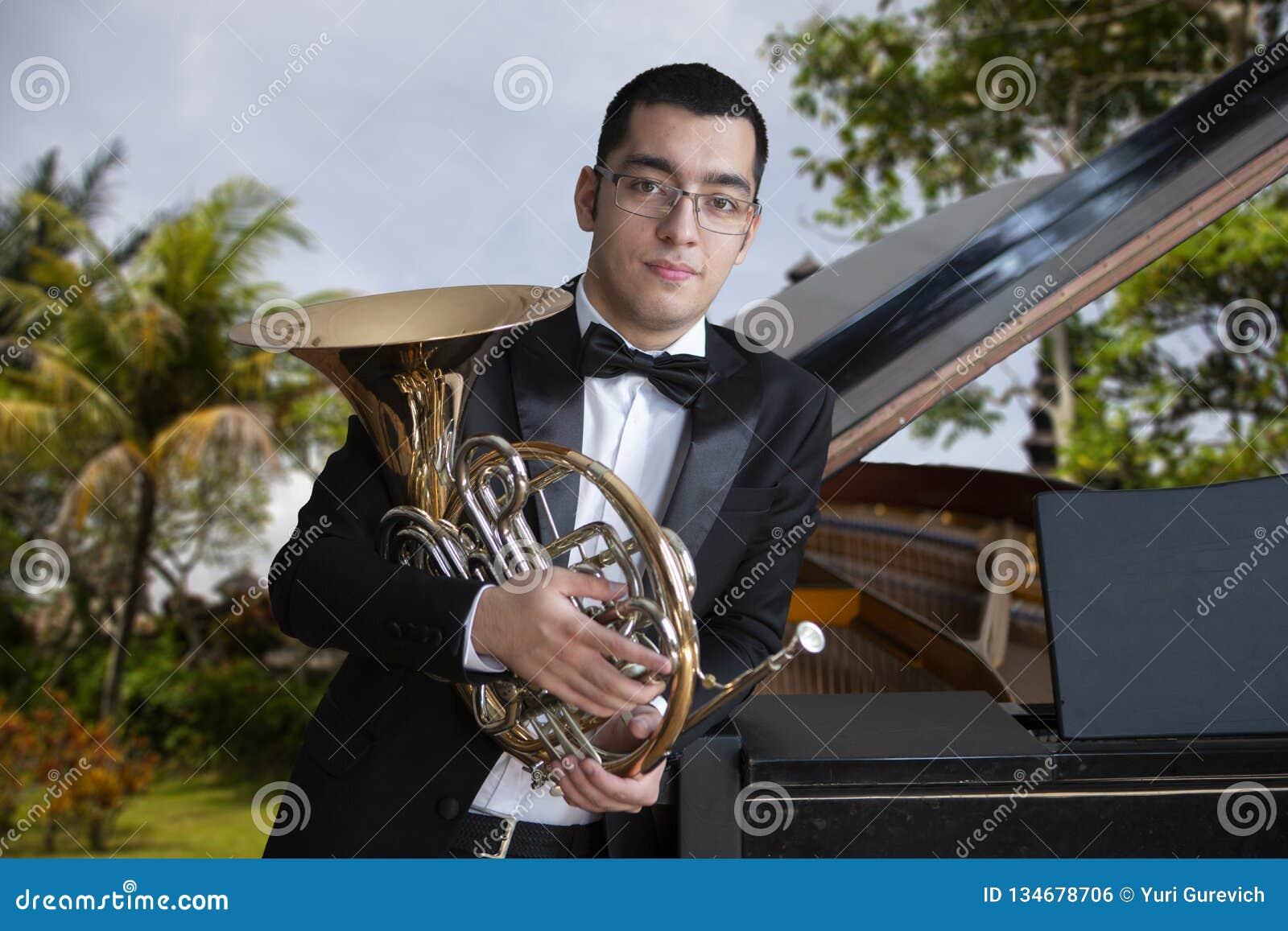 Γαλλικός φορέας κέρατων Όργανο μουσικής ορχηστρών ορείχαλκου παιχνιδιού Hornist Πορτρέτο ενάντια στο σκηνικό του τοπίου θάλασσας