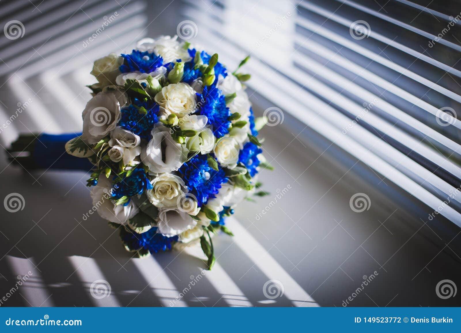 Γαμήλια ανθοδέσμη στο παράθυρο με τους τυφλούς οι ιδιότητες του νεόνυμφου πρόσφατα παντρεμένο ζευγάρι