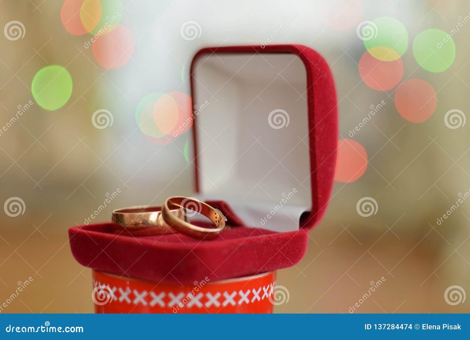 Γαμήλια δαχτυλίδια σε ένα κόκκινο κιβώτιο δώρων με ένα υπόβαθρο bokeh του αστράφτοντας κόμματος