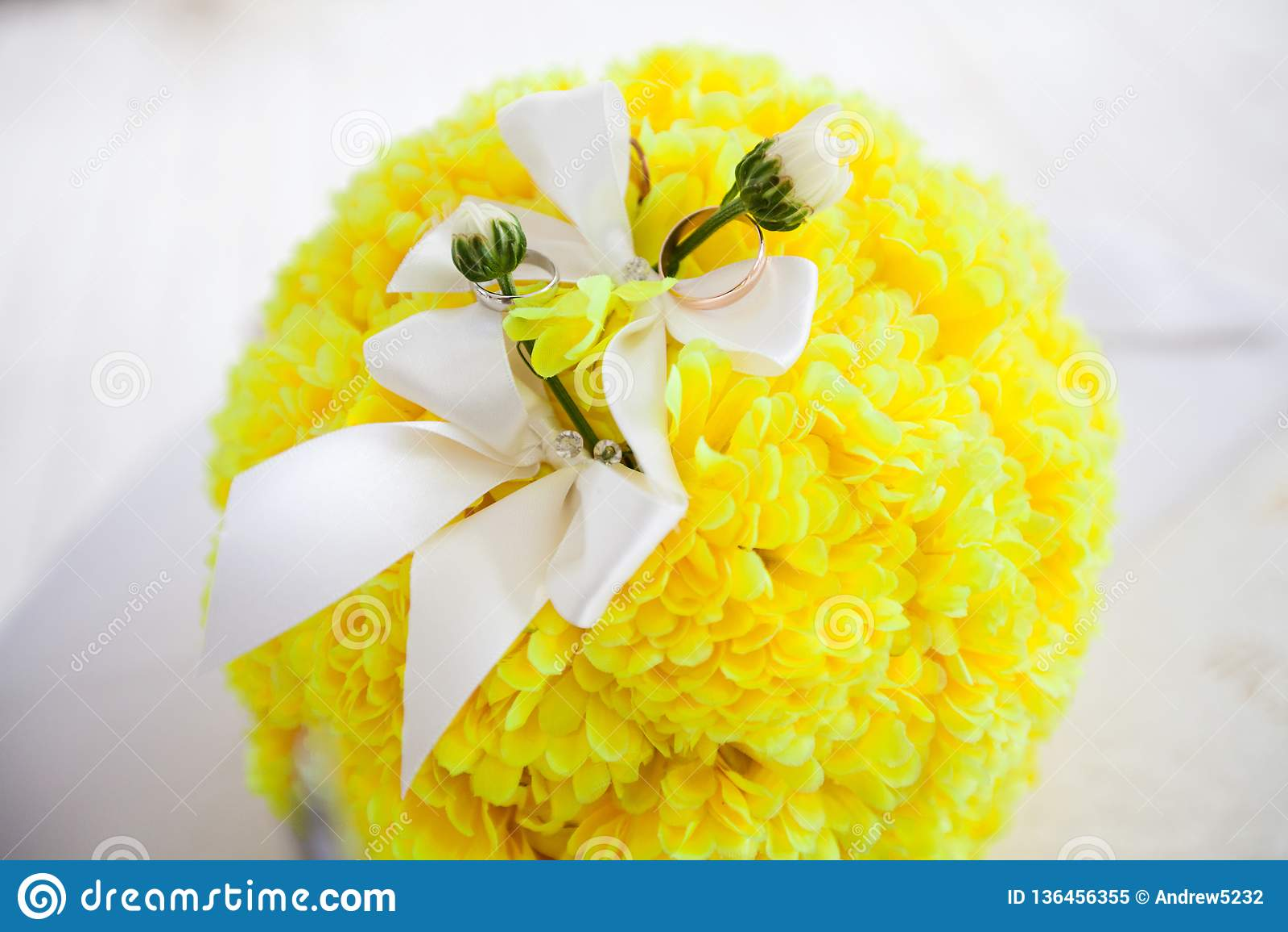 Γαμήλια δαχτυλίδια σε μια ανθοδέσμη των λουλουδιών
