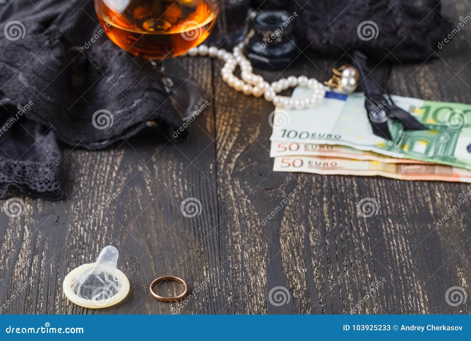 Γαμήλια δαχτυλίδι και προφυλακτικό με τα χρήματα στην πλάτη, έννοια μοιχείας